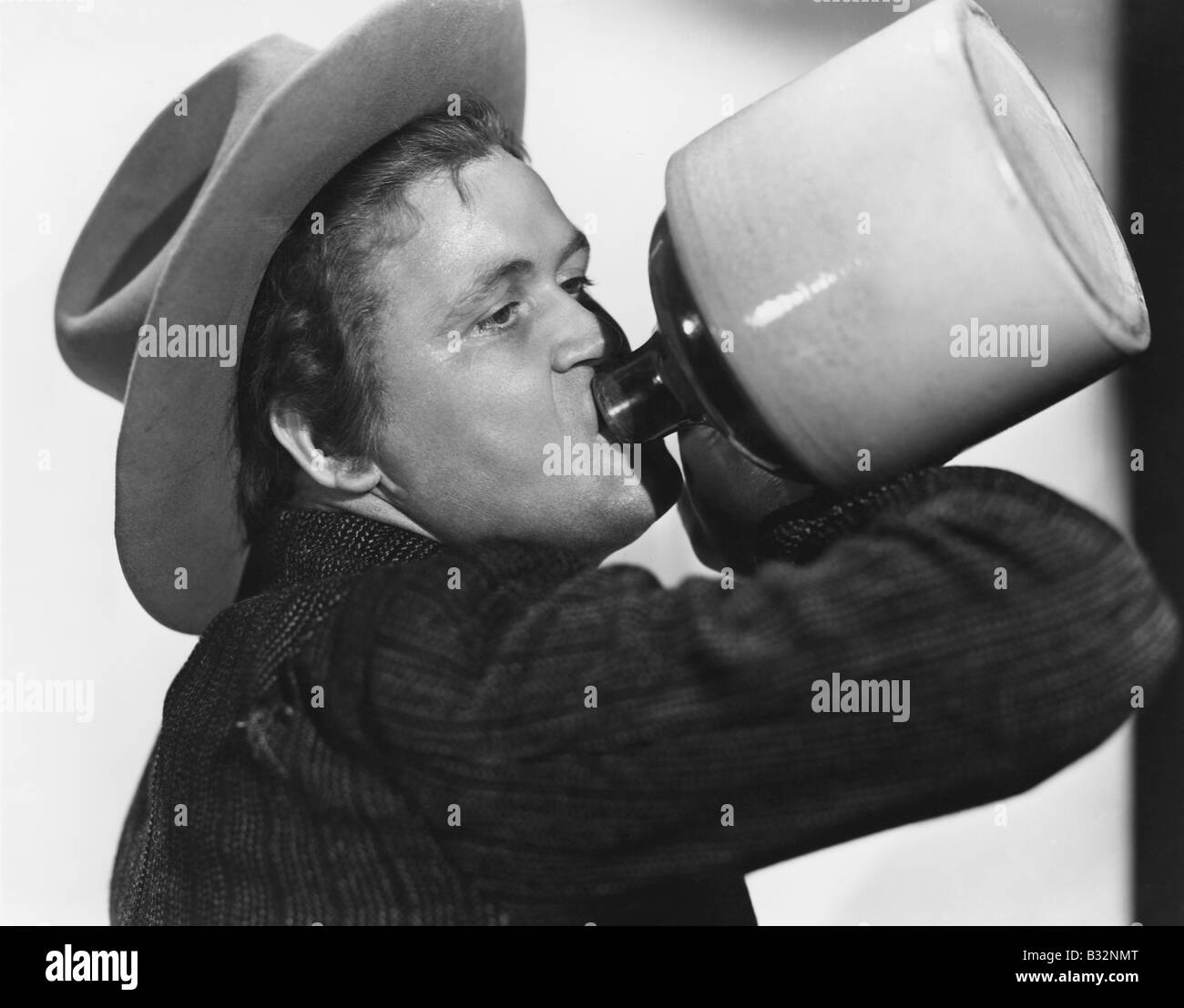Portrait of man drinking from jug - Stock Image