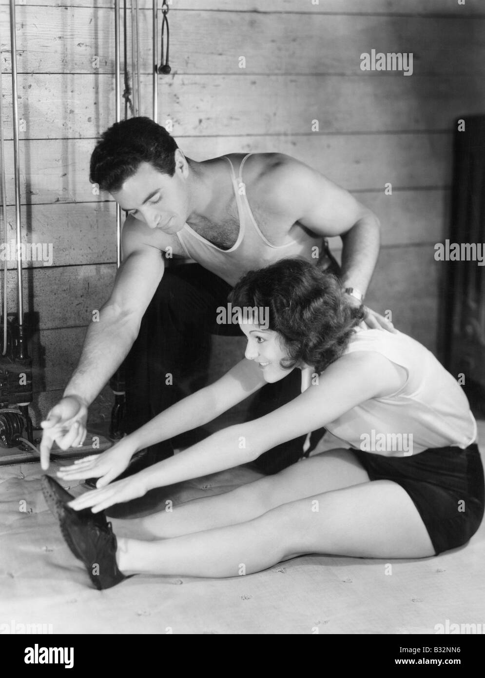 Woman stretching with help from trainer - Stock Image