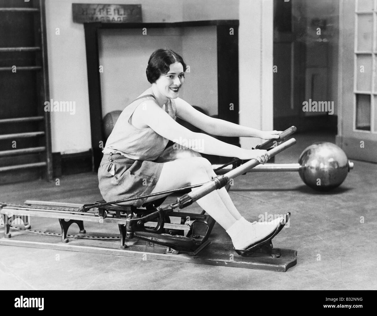 Woman using rowing machine - Stock Image