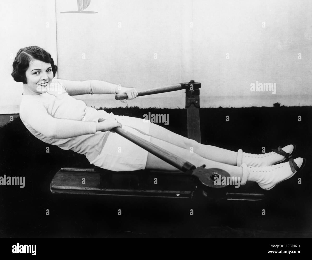 Woman using rowing machine - Stock Image