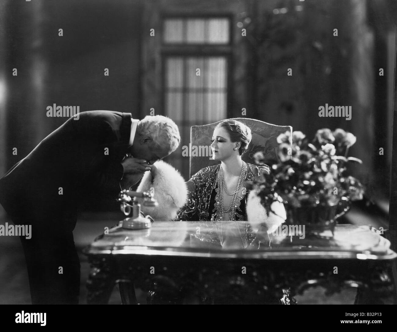 Man kissing hand of woman sitting at desk - Stock Image
