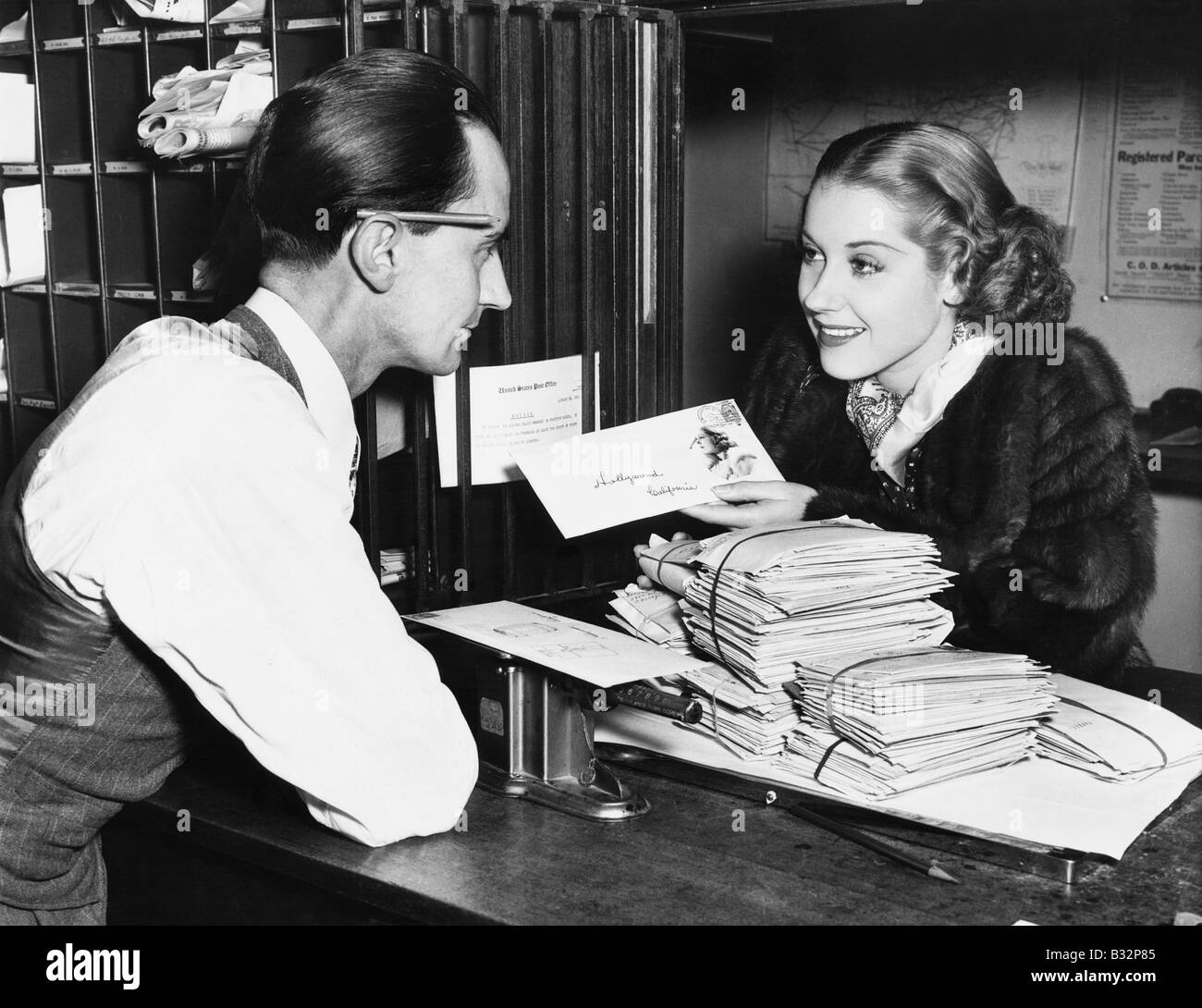 Clerk with woman mailing letter - Stock Image