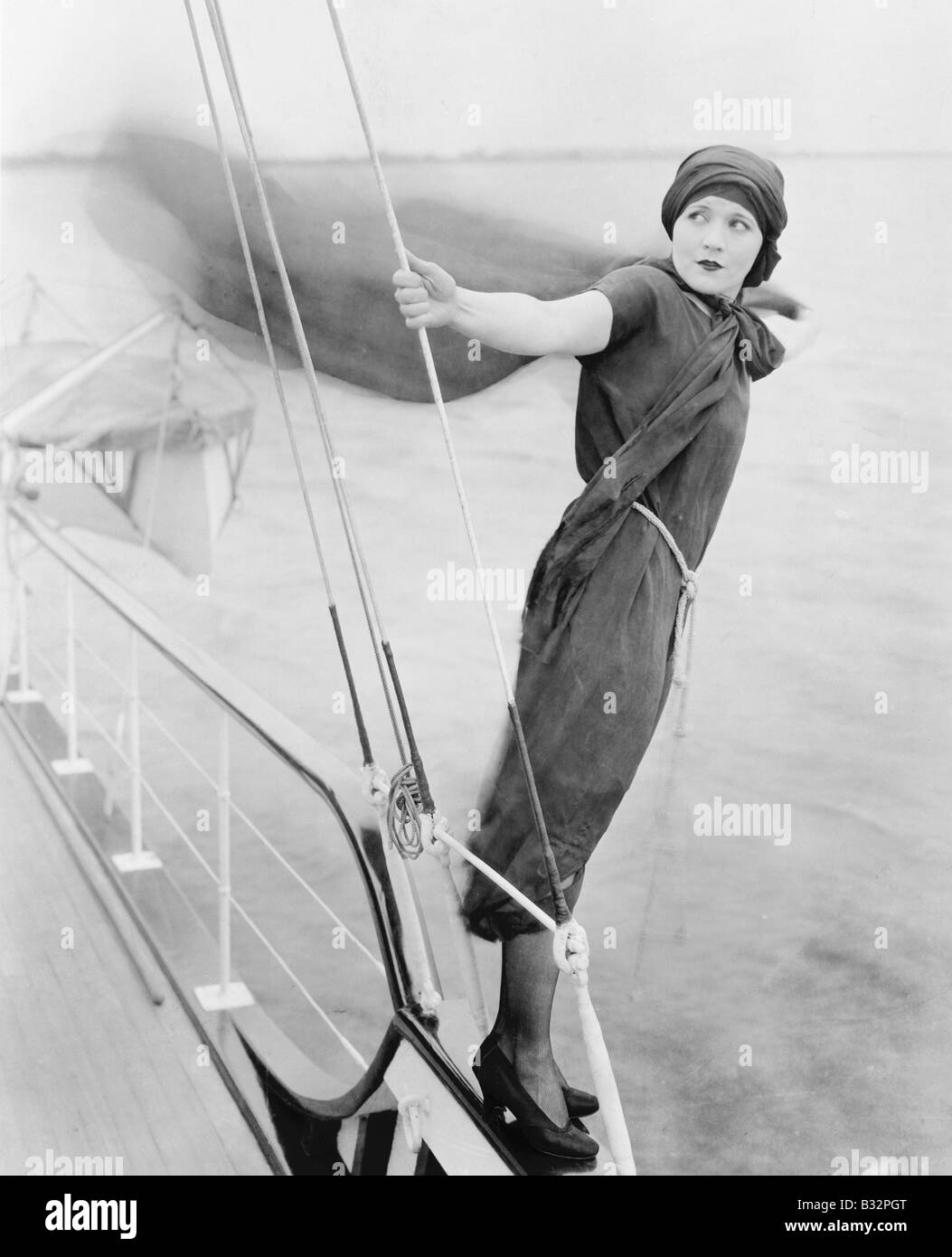 Woman leaning off boat into the wind - Stock Image