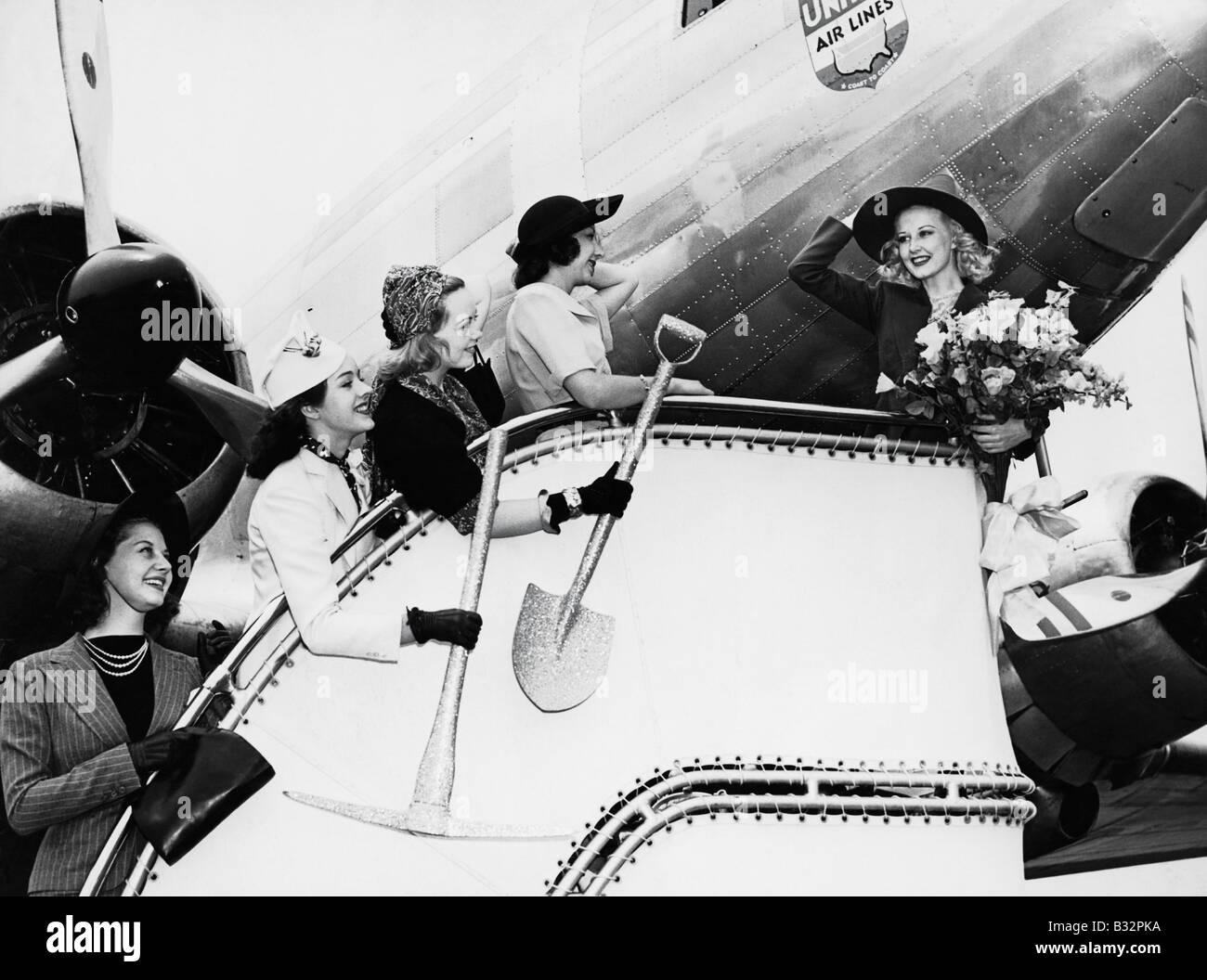 Women sending off friend boarding plane - Stock Image