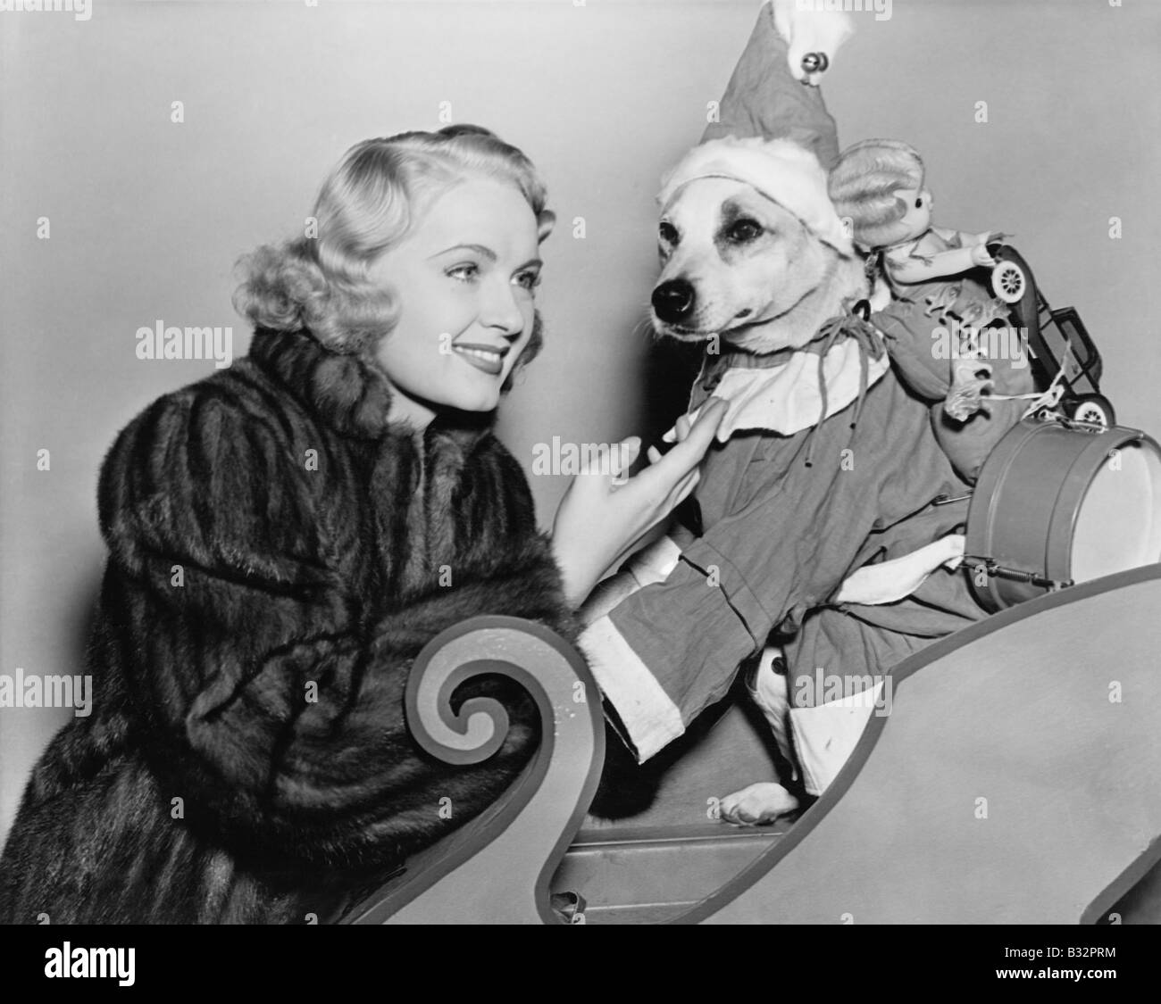 Woman with dog in Christmas outfit - Stock Image