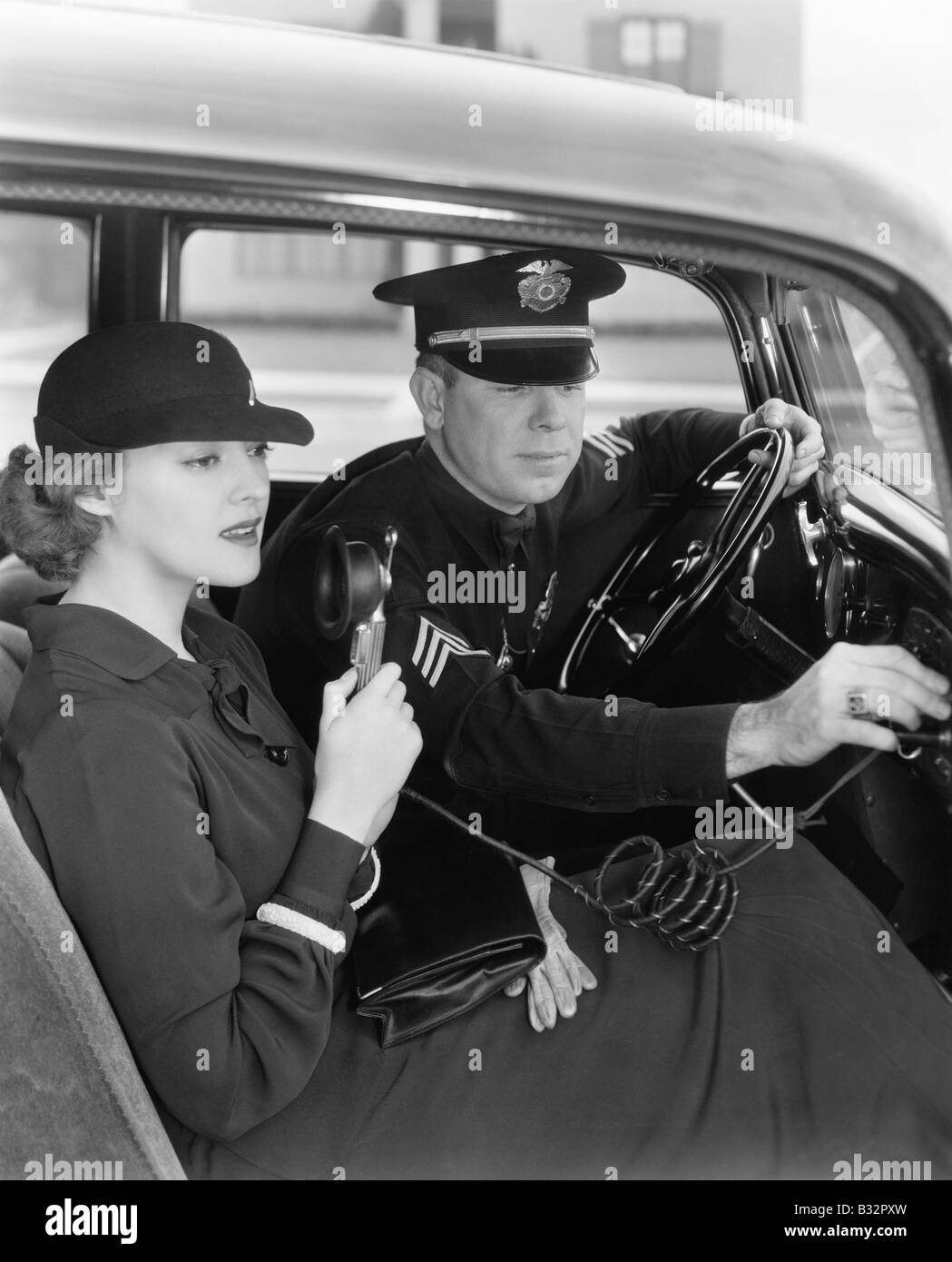 Woman using radio in car with policeman - Stock Image