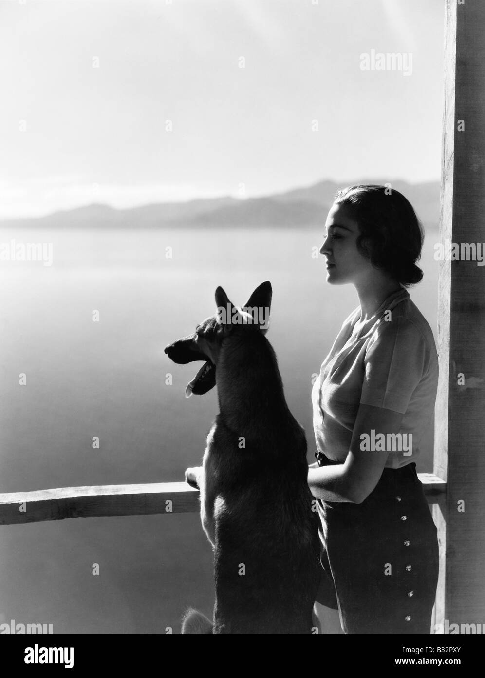 Woman and dog looking out over water - Stock Image