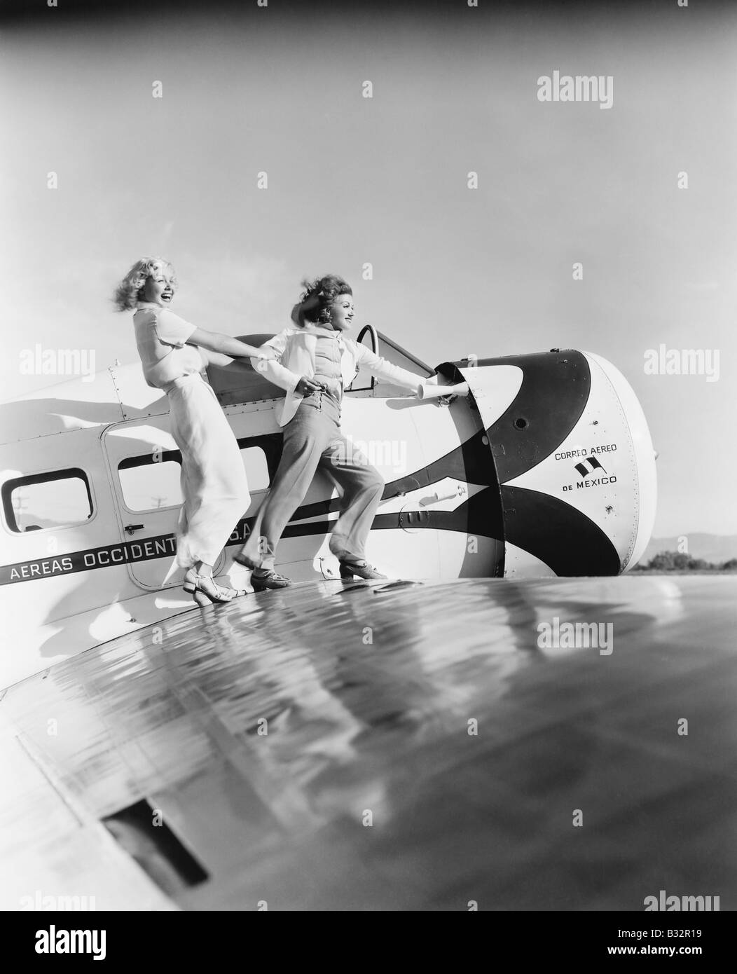 Two women walking on the wing of a plane - Stock Image