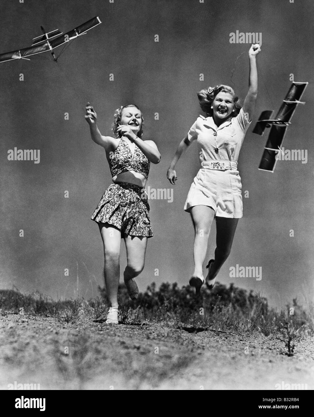 Two women running and playing with model airplanes - Stock Image