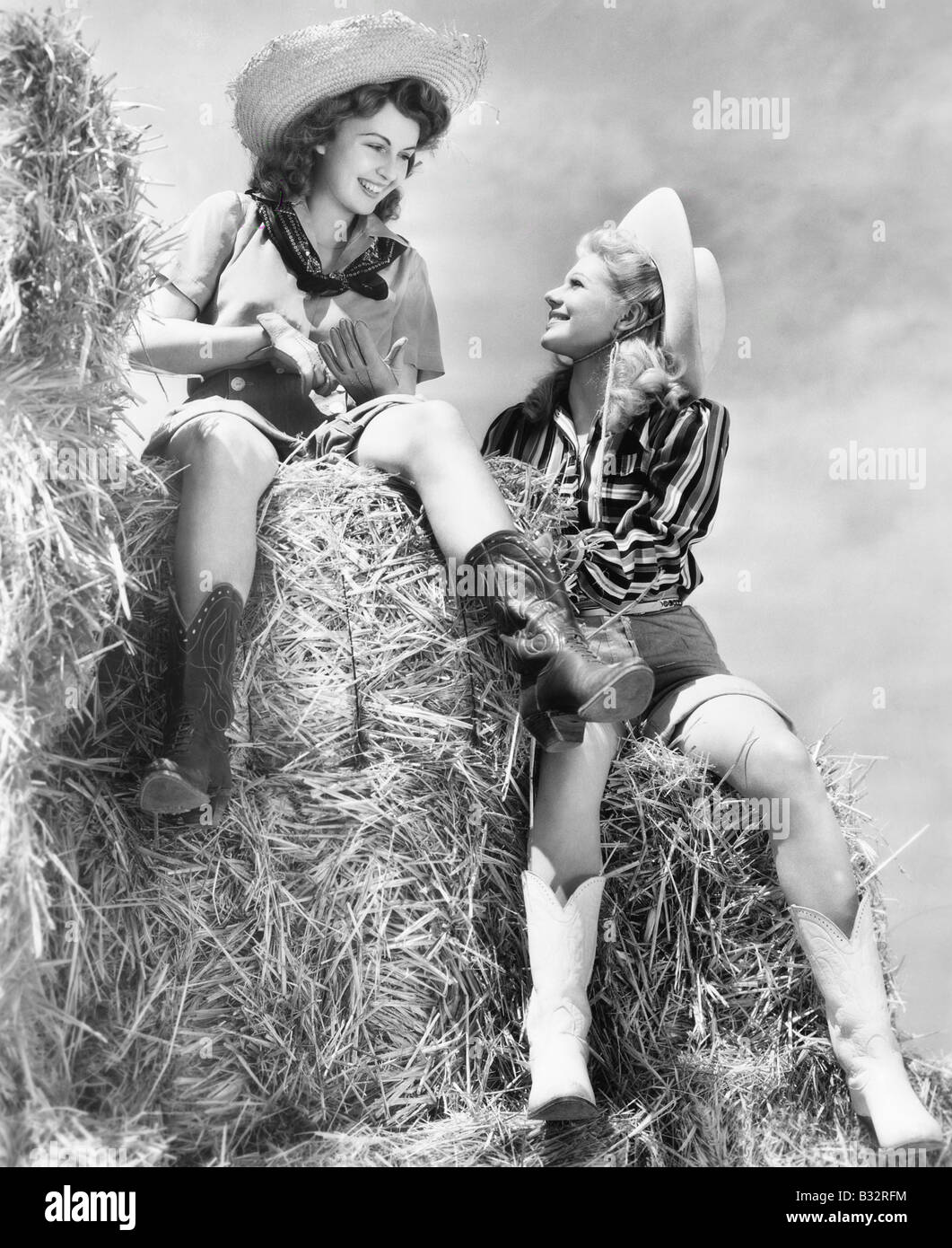 Two women in cowboy hats sitting on a haystack - Stock Image