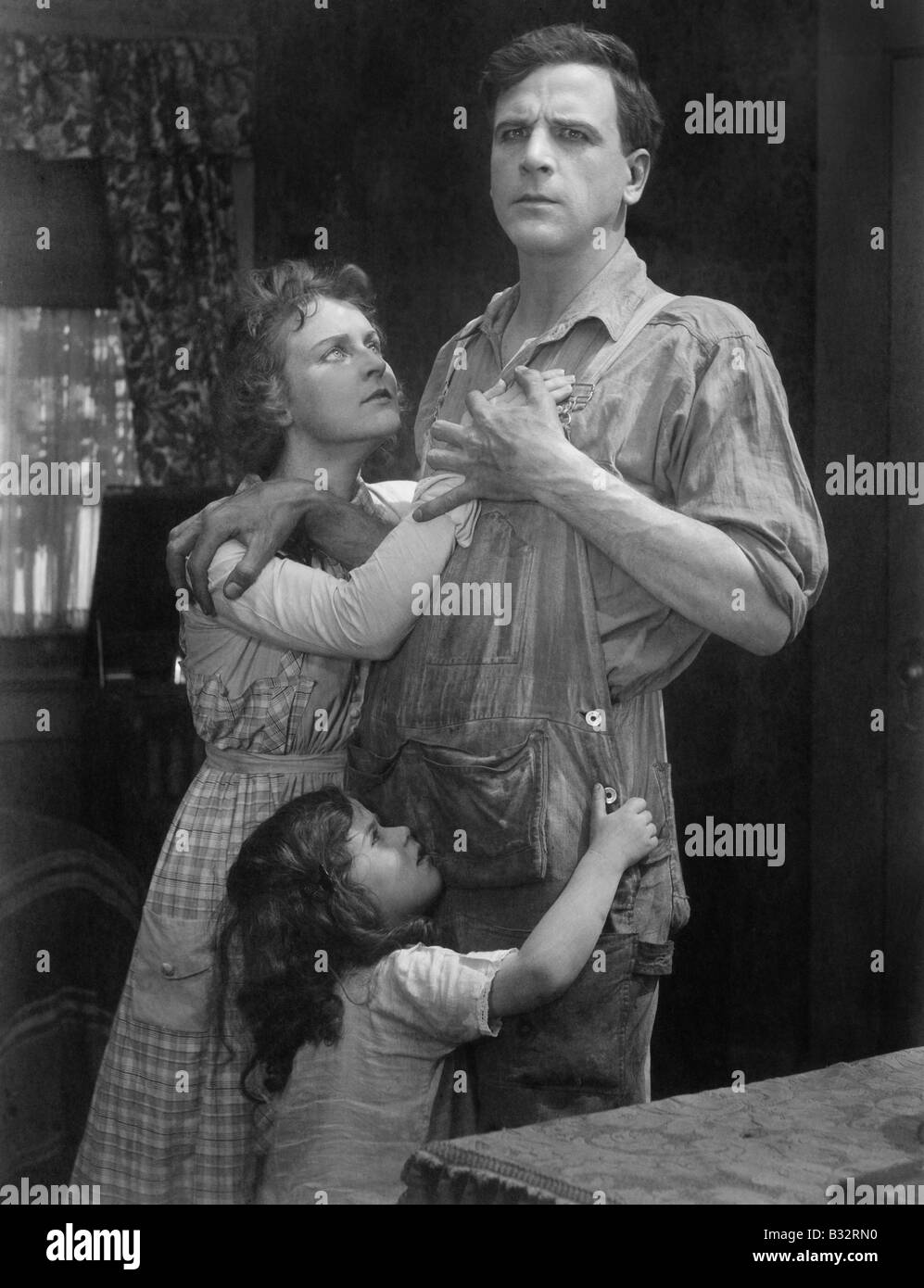 Couple standing embraced with their daughter Stock Photo