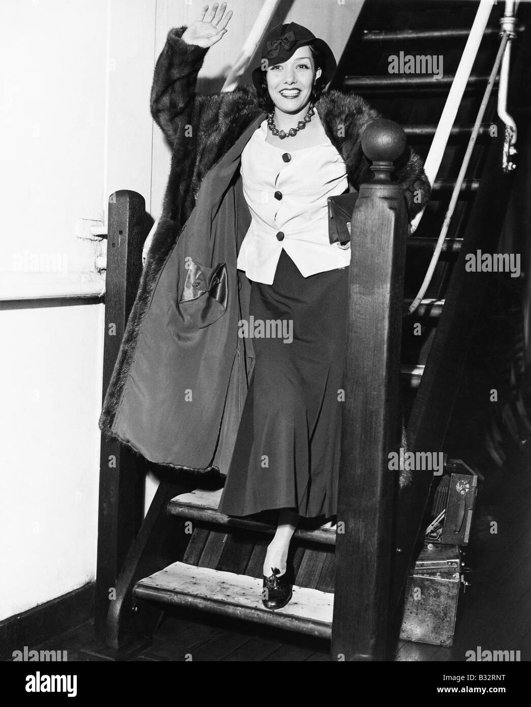 Young woman waving on a staircase and smiling Stock Photo