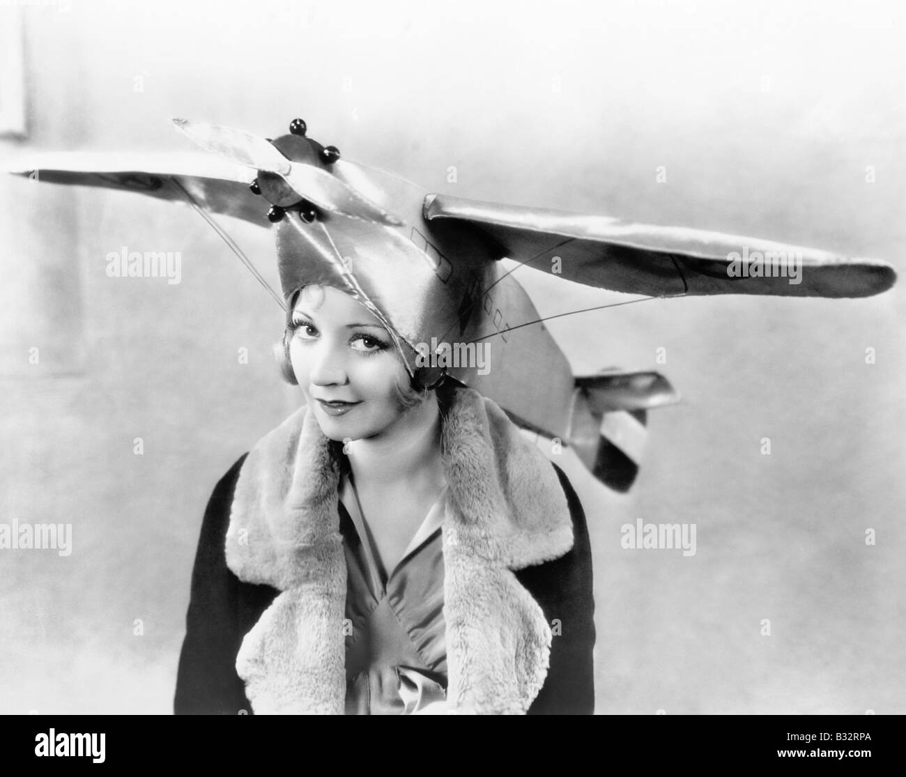 Portrait young woman wearing airplane shaped cap - Stock Image