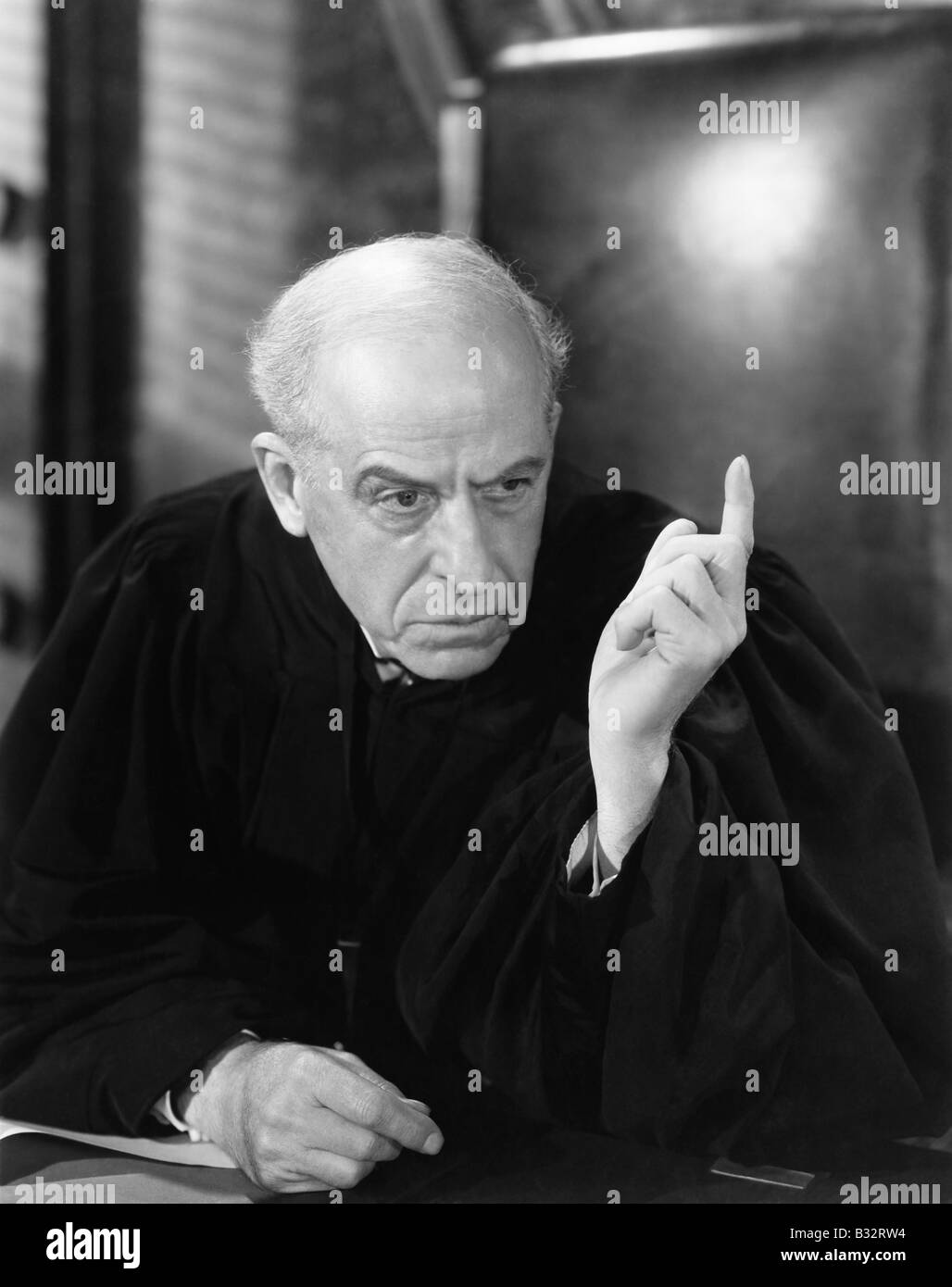 Judge in a courtroom pointing his finger up - Stock Image