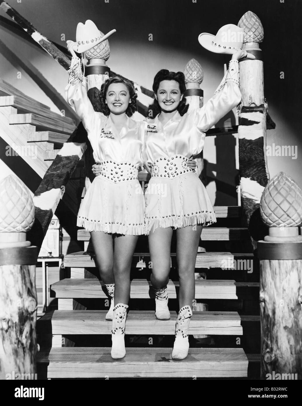 Two young women stepping down a staircase waving their western hats - Stock Image