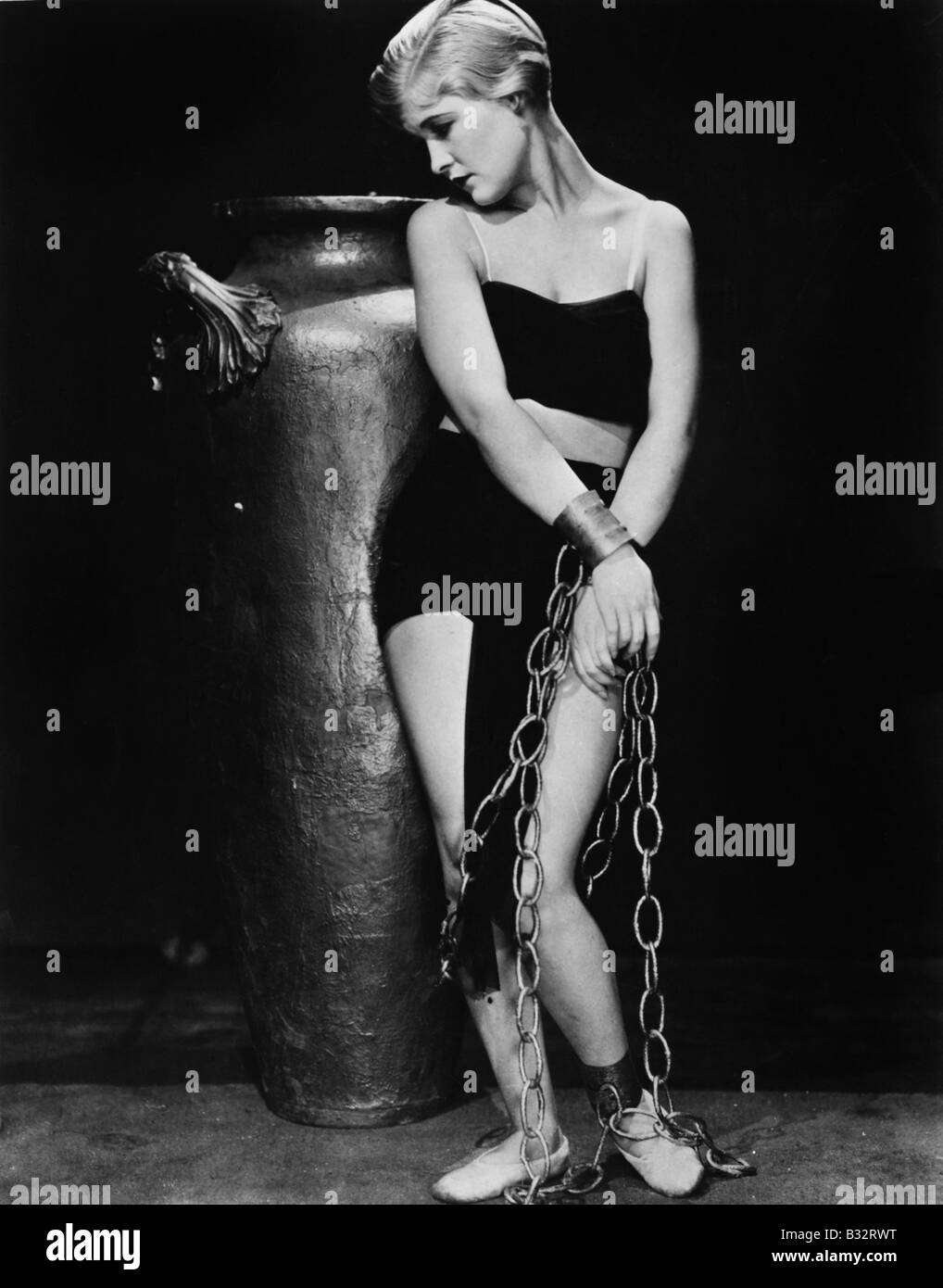 Woman chained in front of a big vase Stock Photo