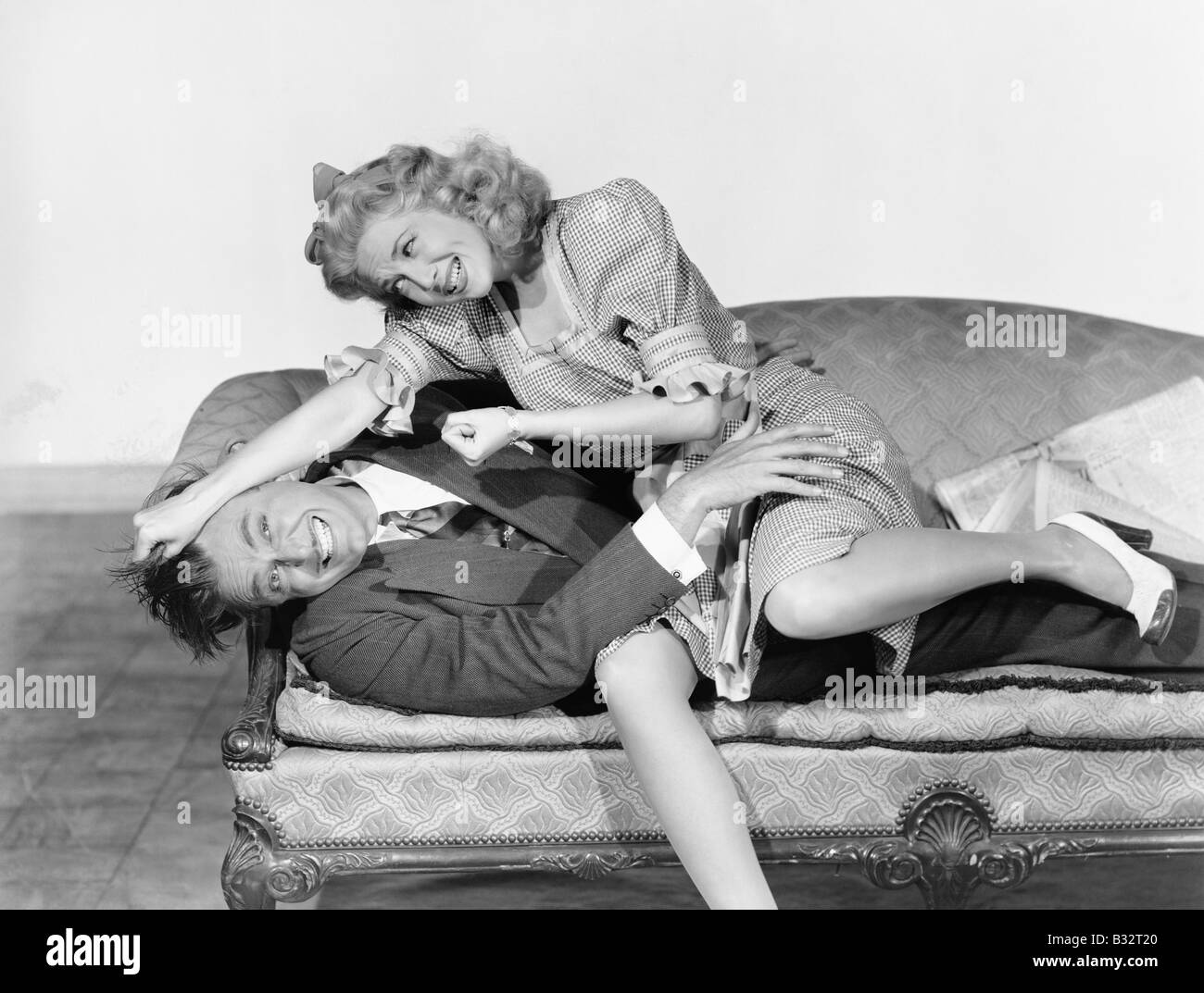 Couple having a playful fight on a couch Stock Photo