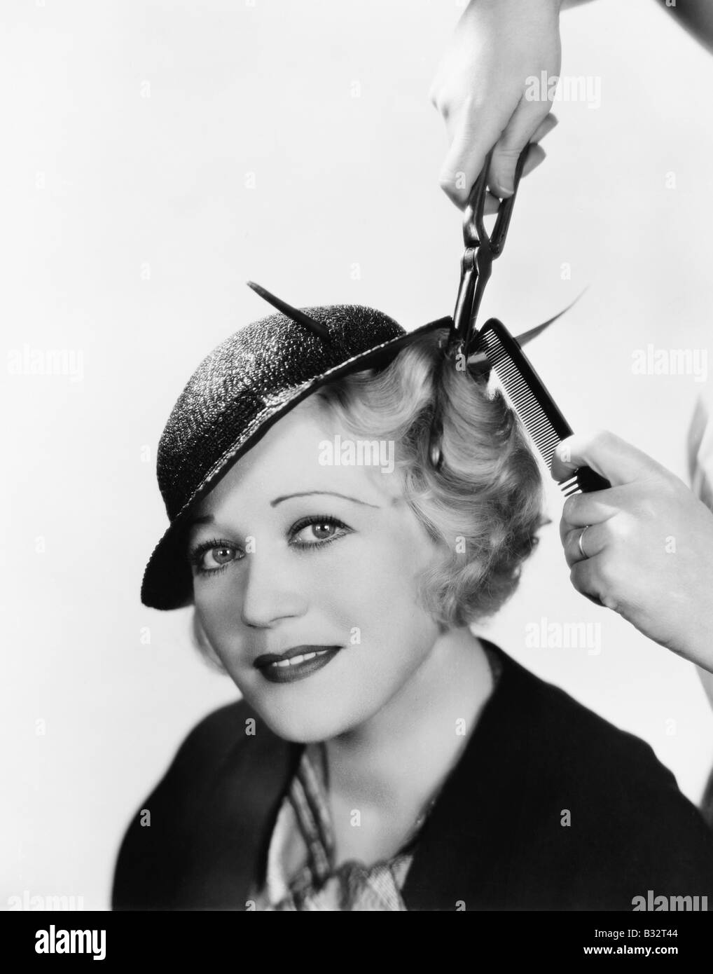 Portrait of a young woman getting her hair curled with an iron - Stock Image