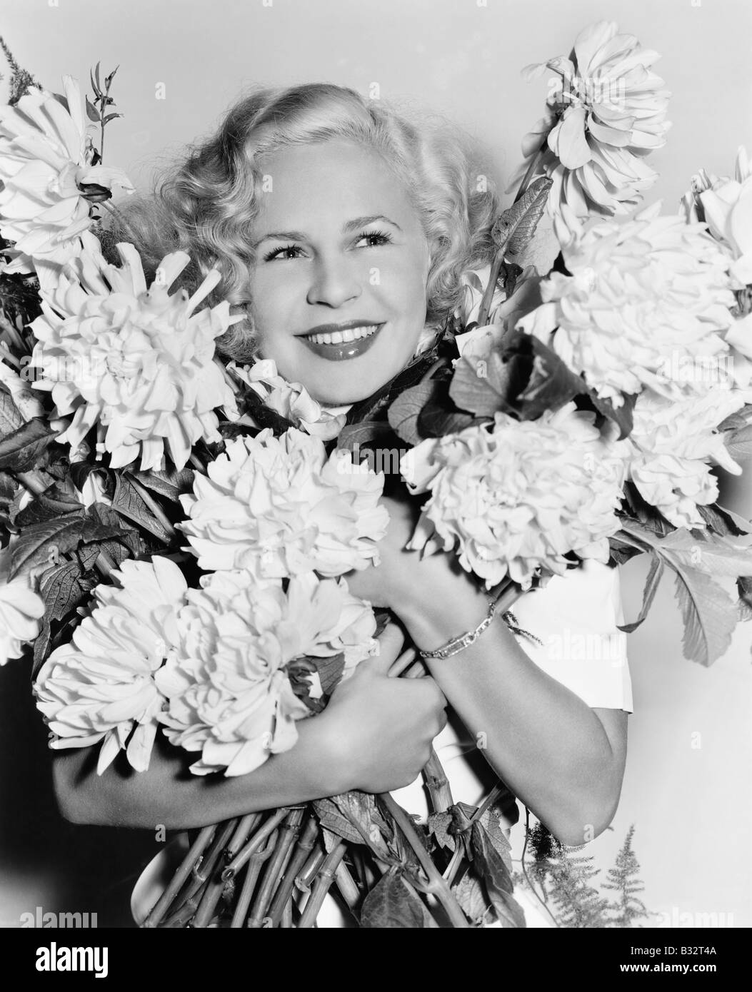 Portrait of a young woman holding a bunch of flowers looking happy - Stock Image