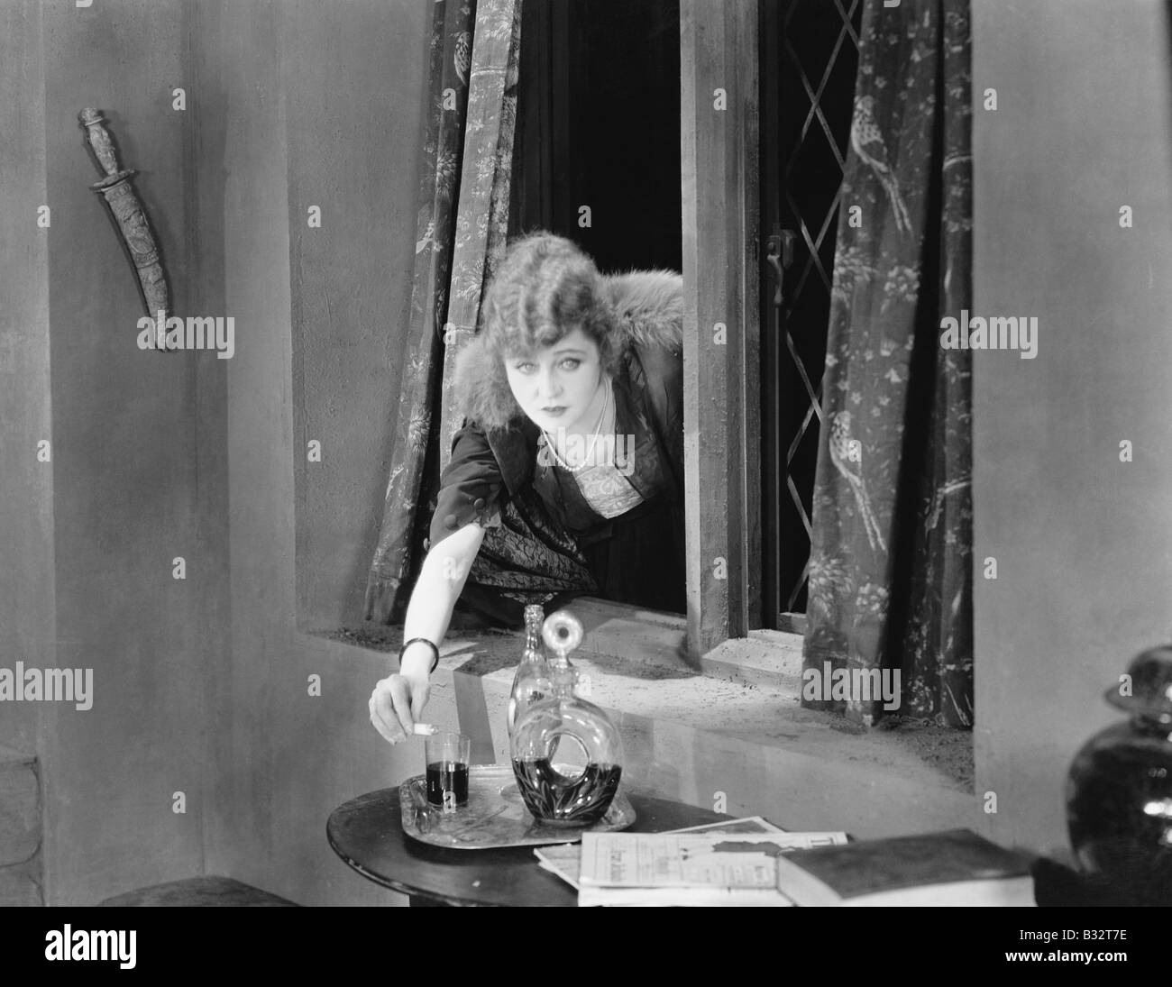 Portrait of a young woman reaching through a window and pouring poison into a glass - Stock Image