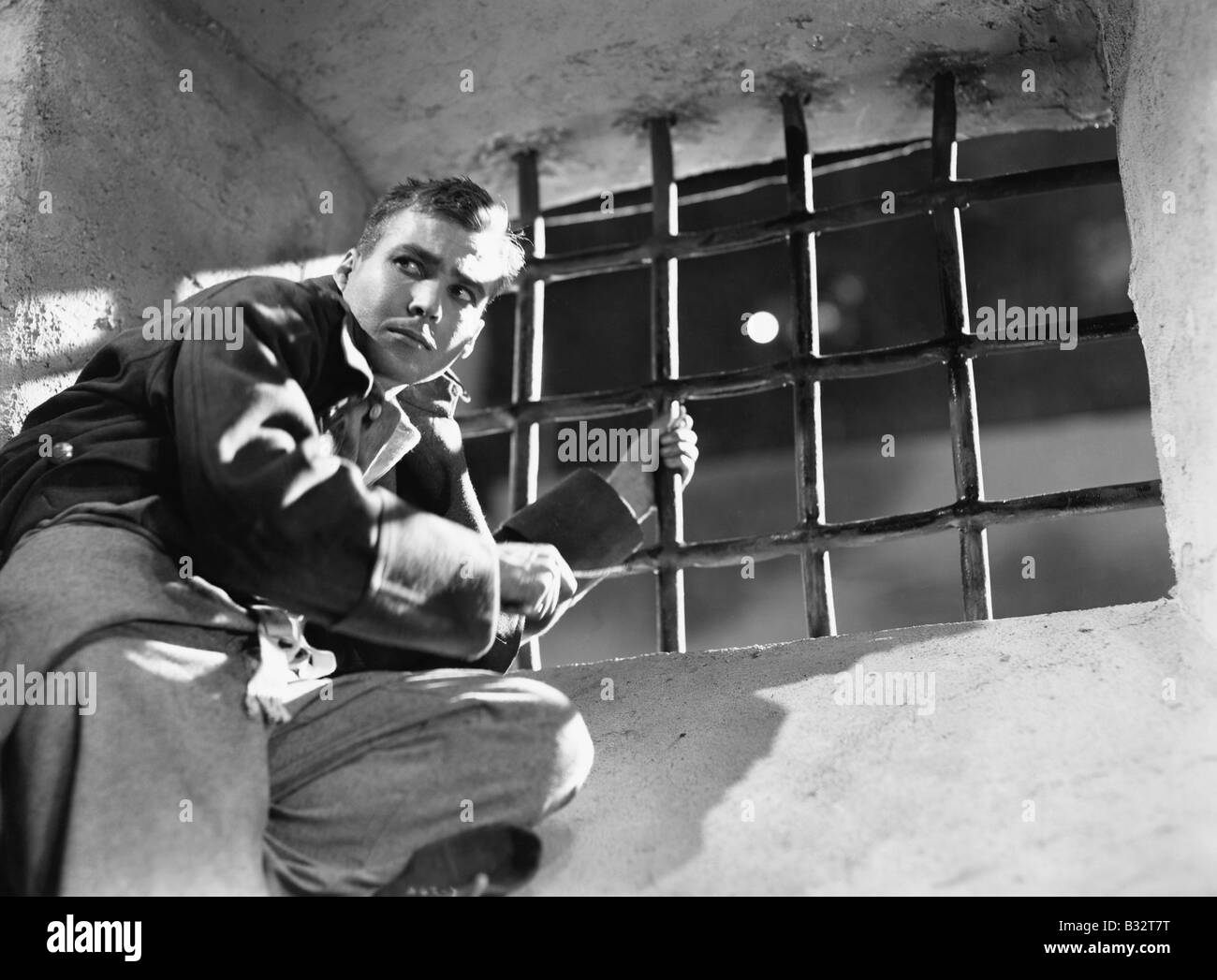 Low angle view of a young man trying to escape from a prison cell - Stock Image