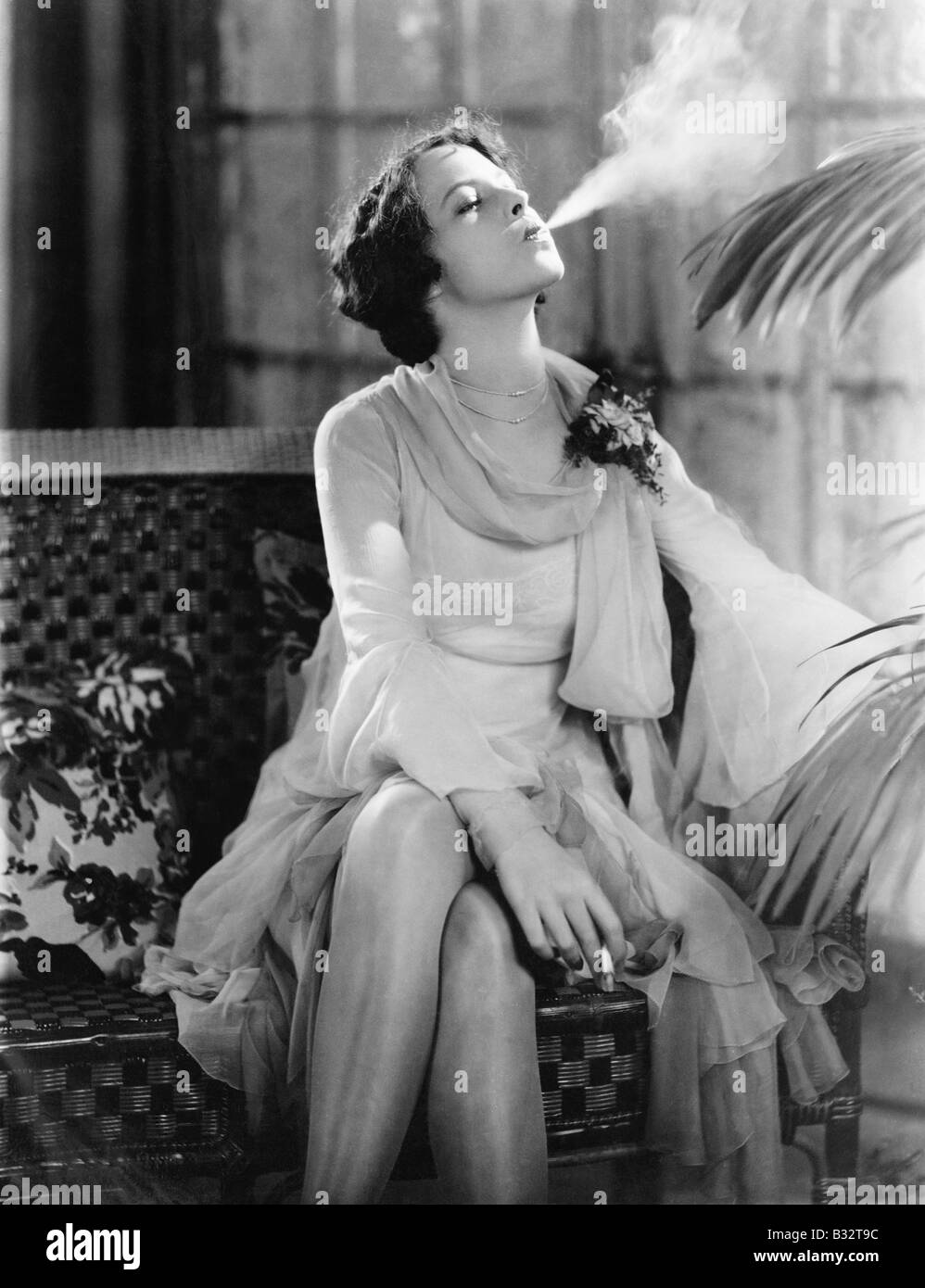 Young woman sitting on a couch smoking a cigarette - Stock Image
