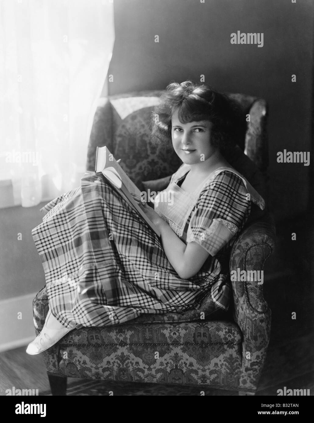 Portrait of a young woman sitting in an armchair and holding a book - Stock Image