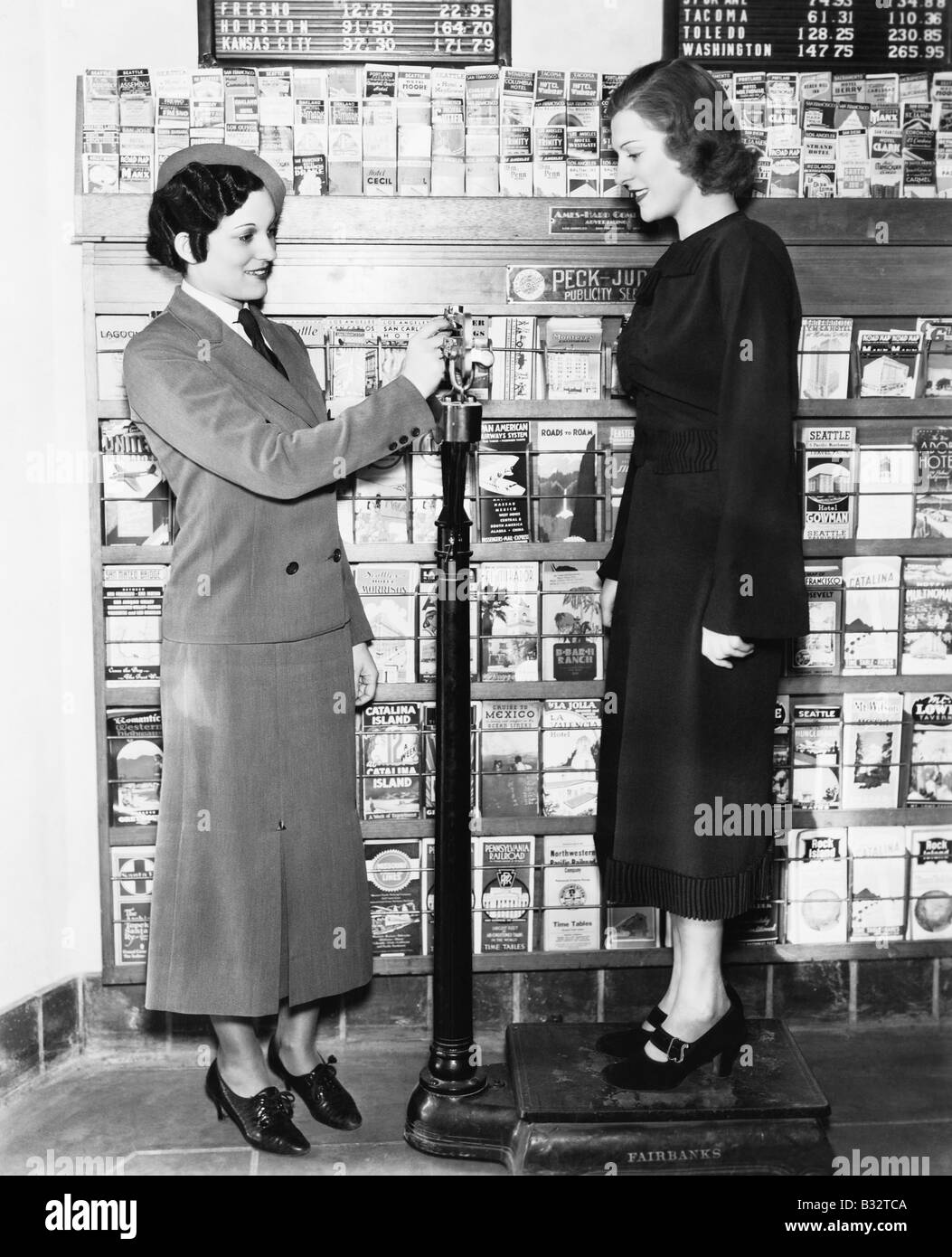 Profile of a young woman in an uniform measuring weight of another young woman on a weighing scale - Stock Image