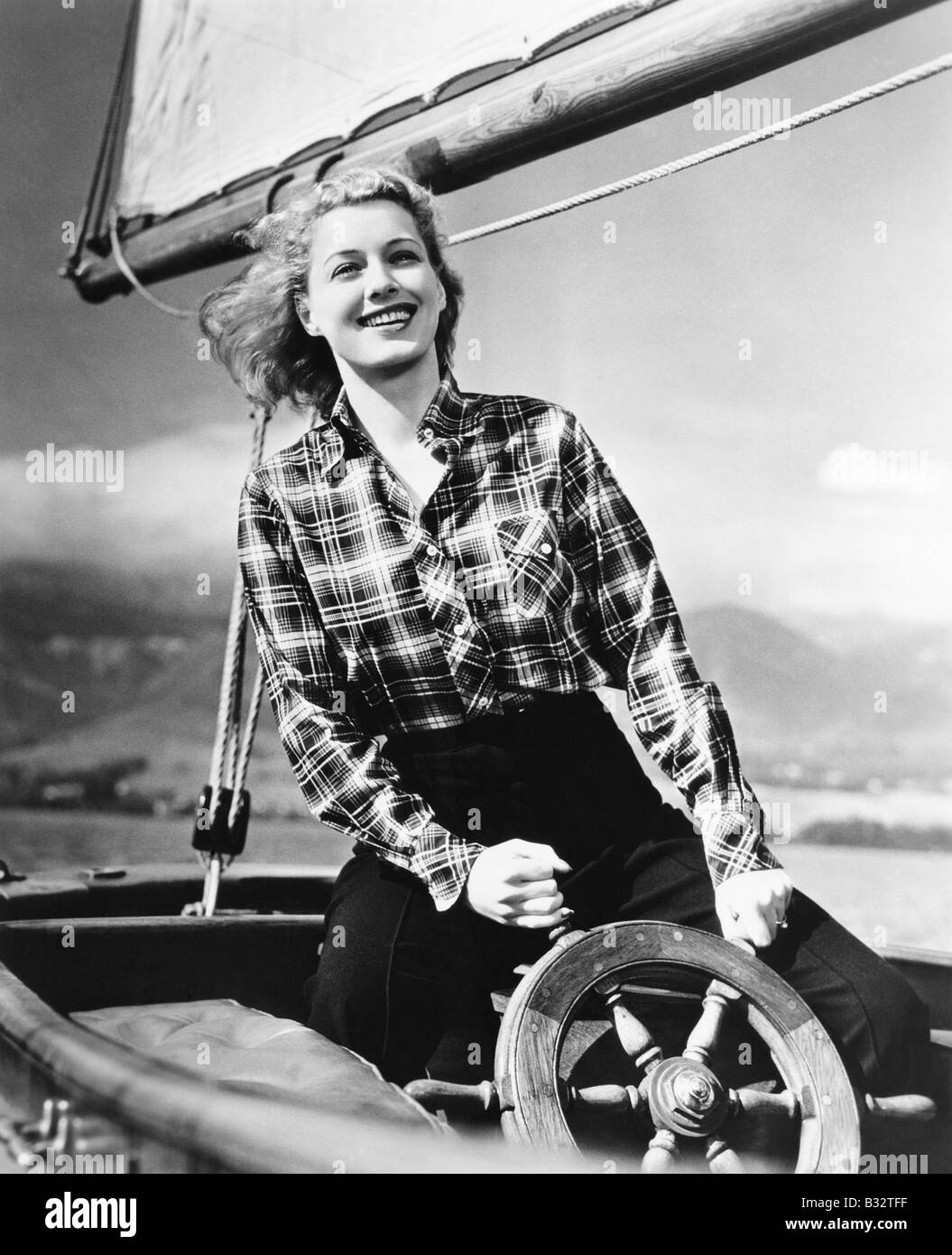 Young woman standing at the helm of a sailboat and holding the wheel - Stock Image