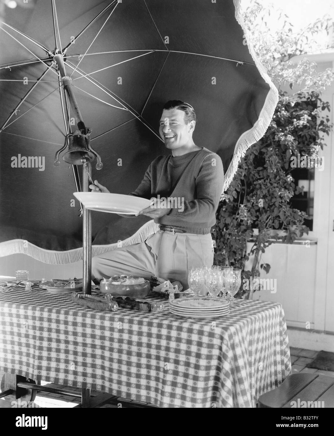 Man standing at a picnic table and holding a plate - Stock Image
