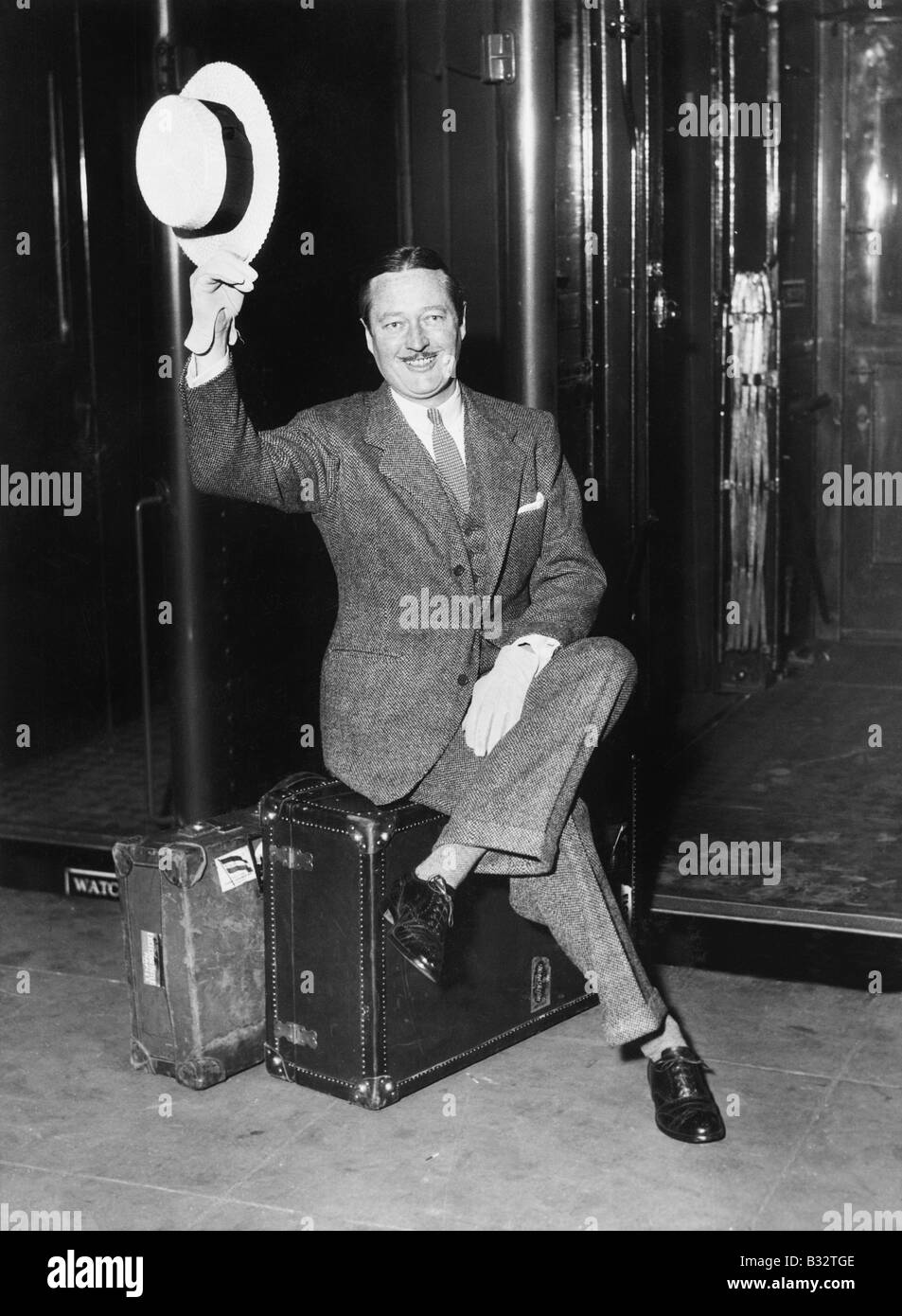 Portrait of a businessman sitting on his suitcases on a platform in front of a train - Stock Image