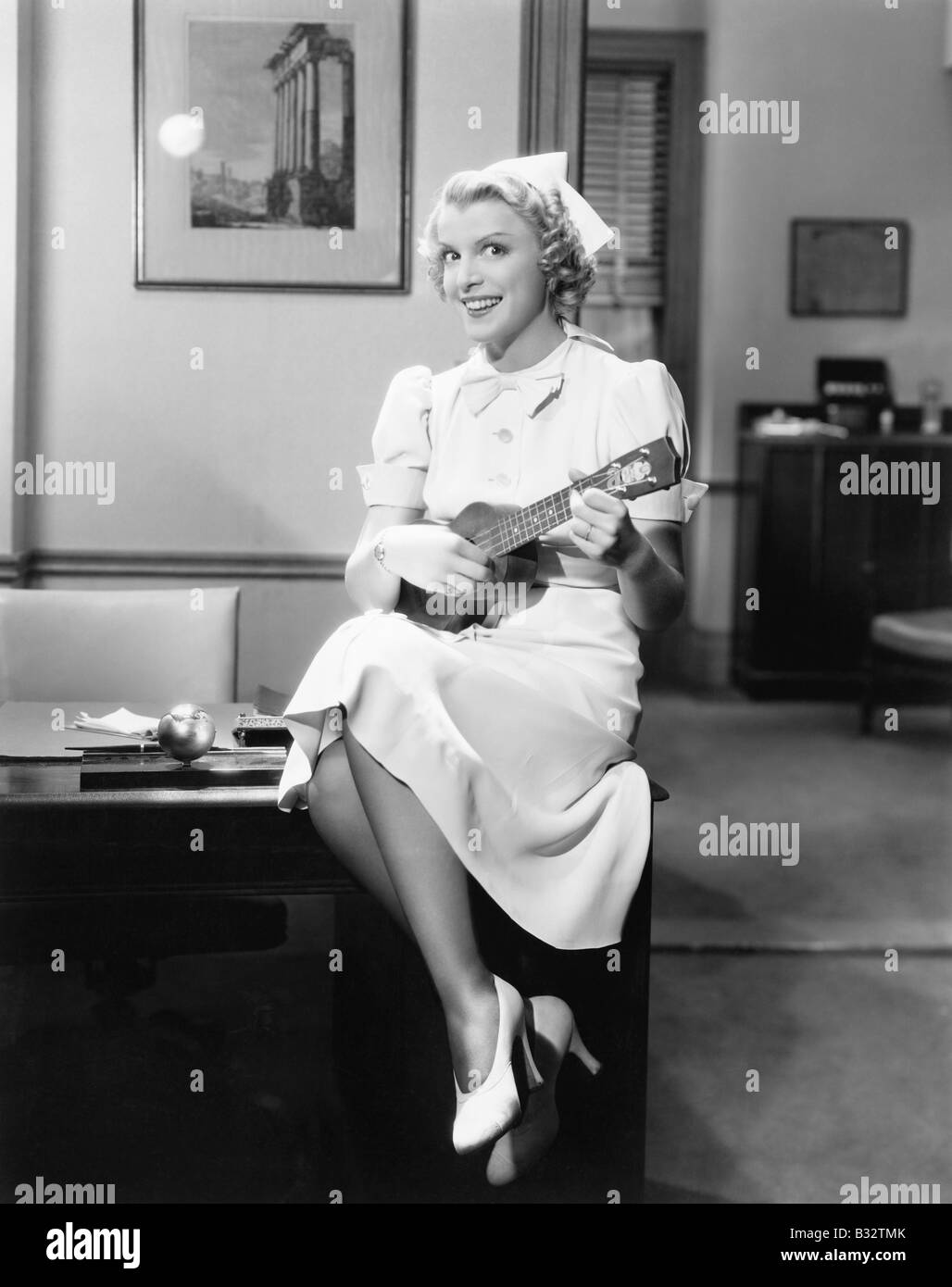 Portrait of a female nurse sitting on a table and playing a guitar - Stock Image