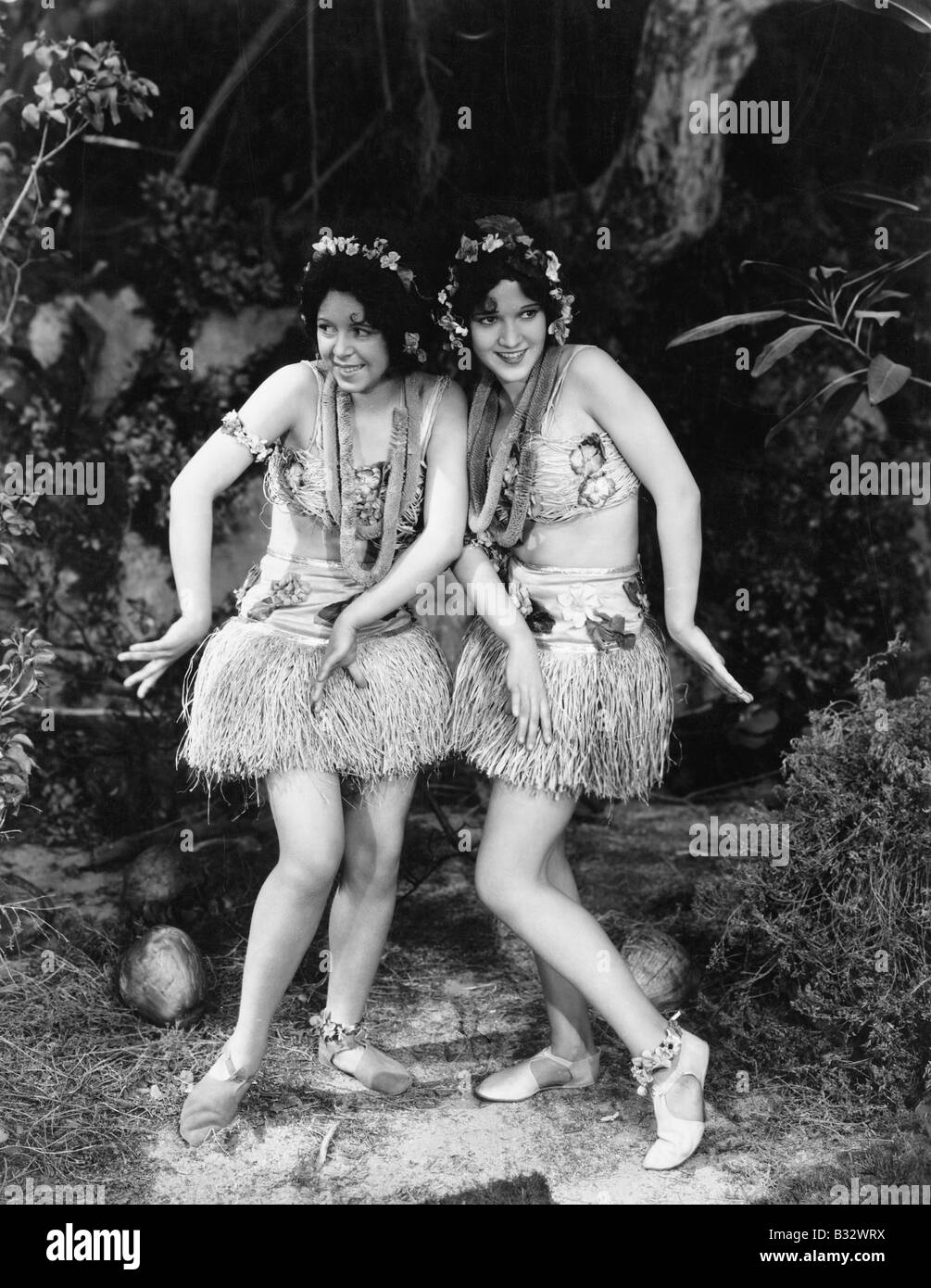 Two women dancing in grass skirts - Stock Image