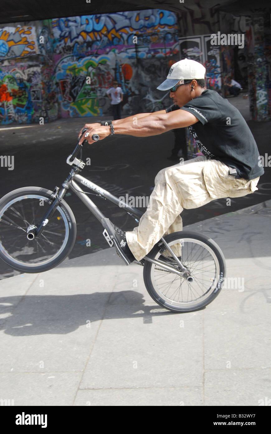 BMX wheelie urban sport London grime graffiti city concrete slacker - Stock Image