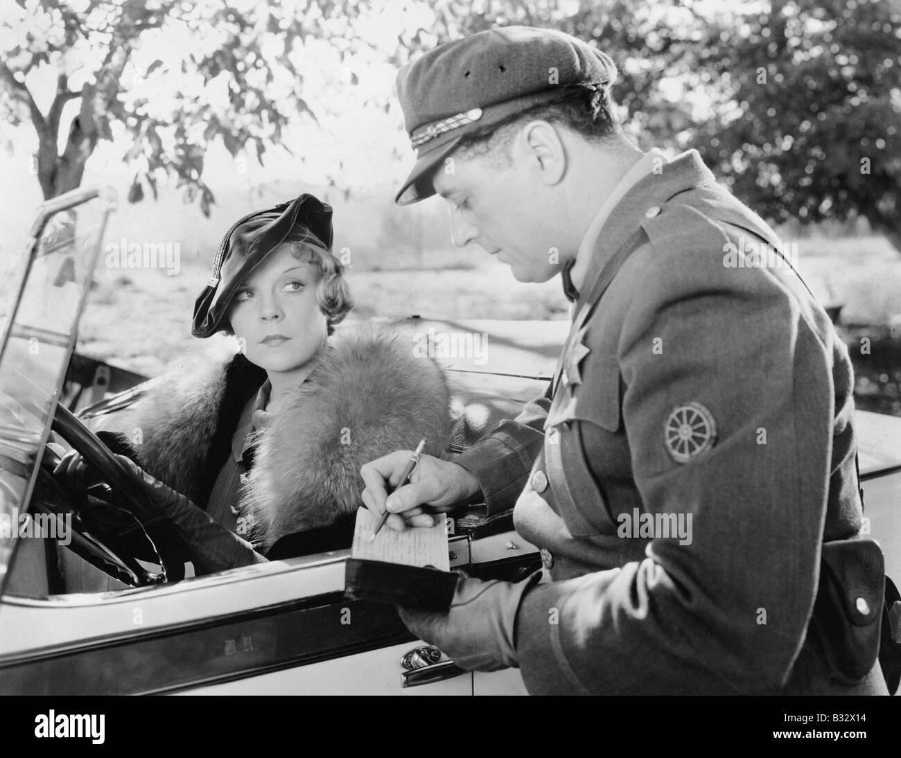 Woman getting a ticket from a policeman - Stock Image