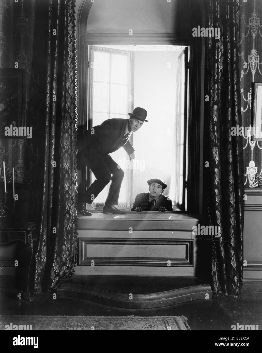 Two men breaking into an apartment - Stock Image
