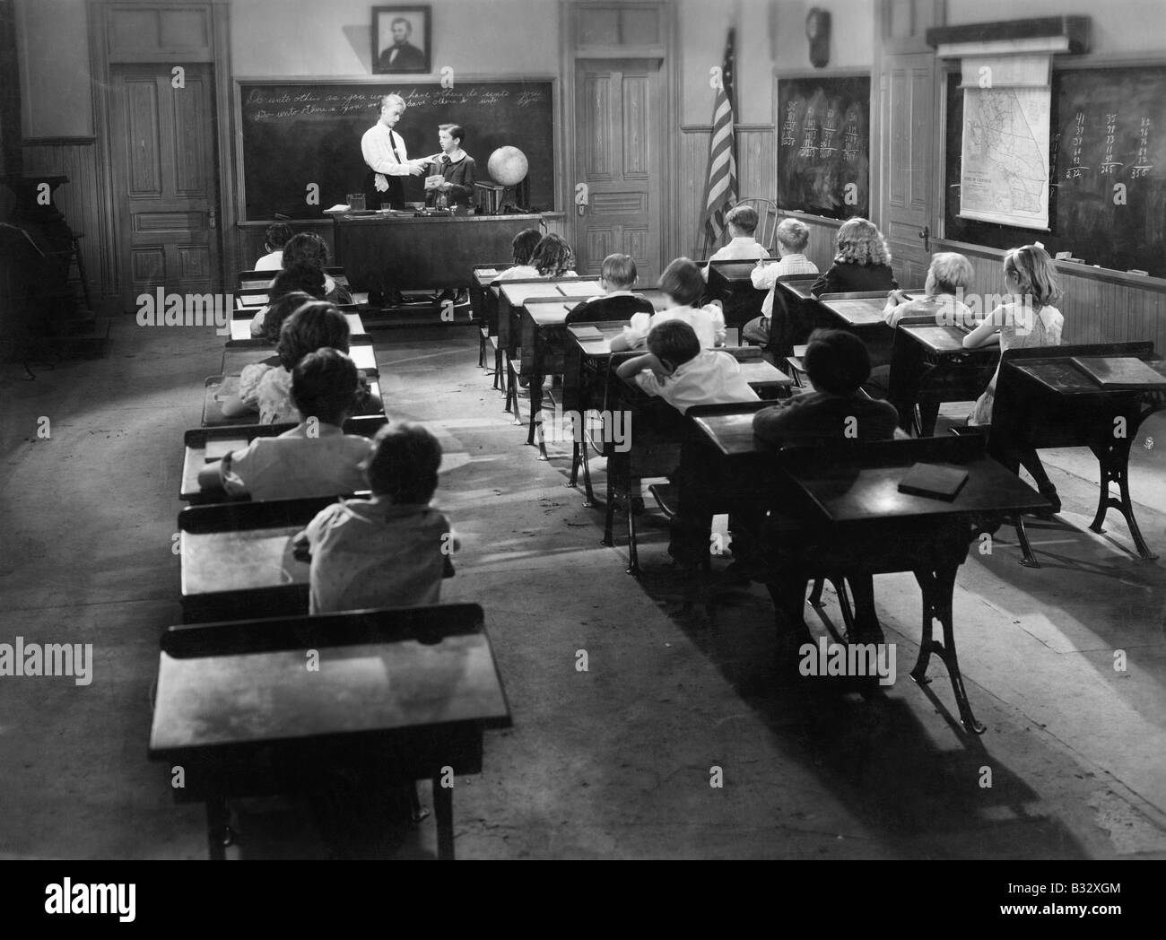 Children in a class room with a teacher - Stock Image