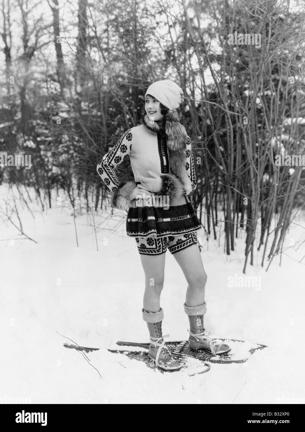 Young woman walking with snow shoes through the woods - Stock Image
