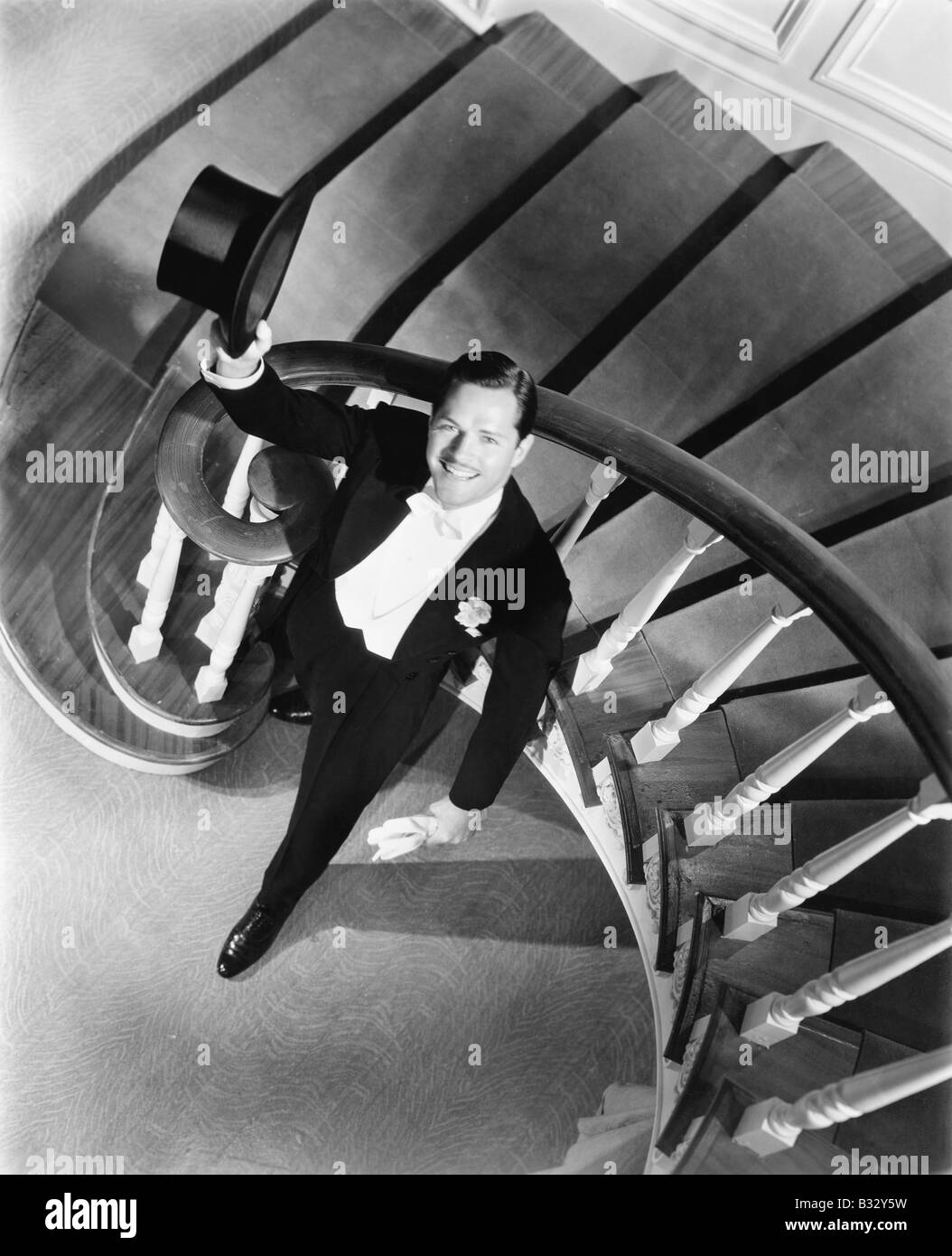 Elegant man looking up from the bottom of a staircase - Stock Image