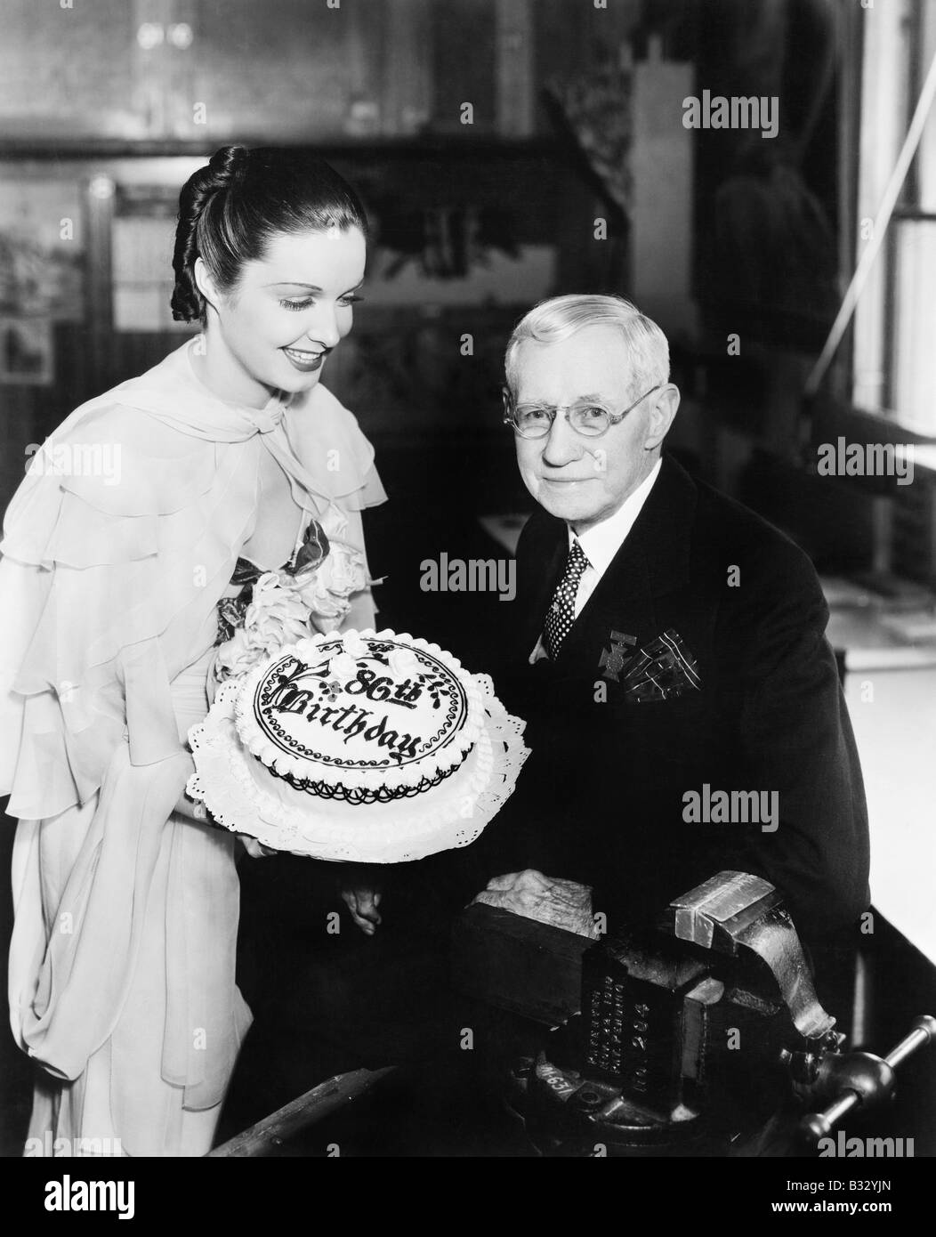 Young woman presenting a birthday cake to an elderly man - Stock Image