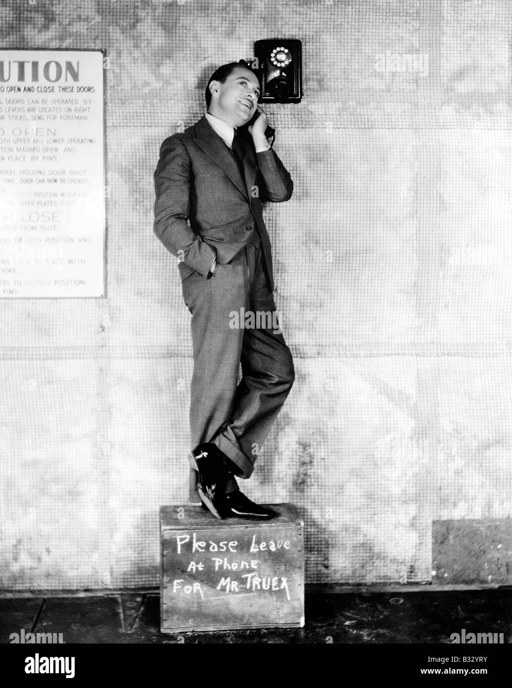 Man standing on a box to reach the telephone - Stock Image