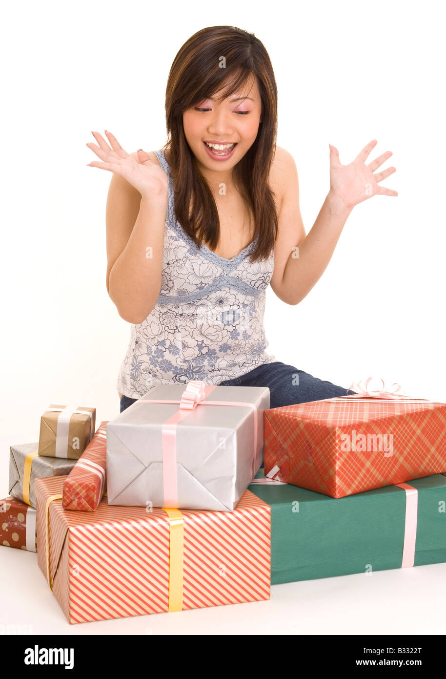A young asian woman is excited as she has a huge pile of gifts to open