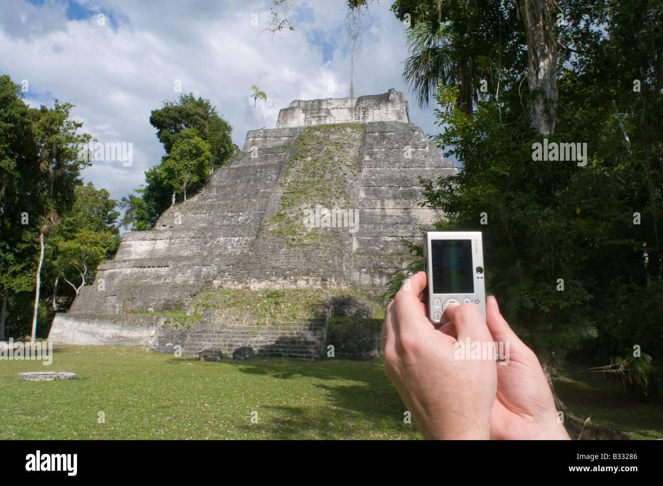 Tourist using a digital camera to photograph a Mayan temple at Yaxha nr Tikal Guatemala - Stock Image