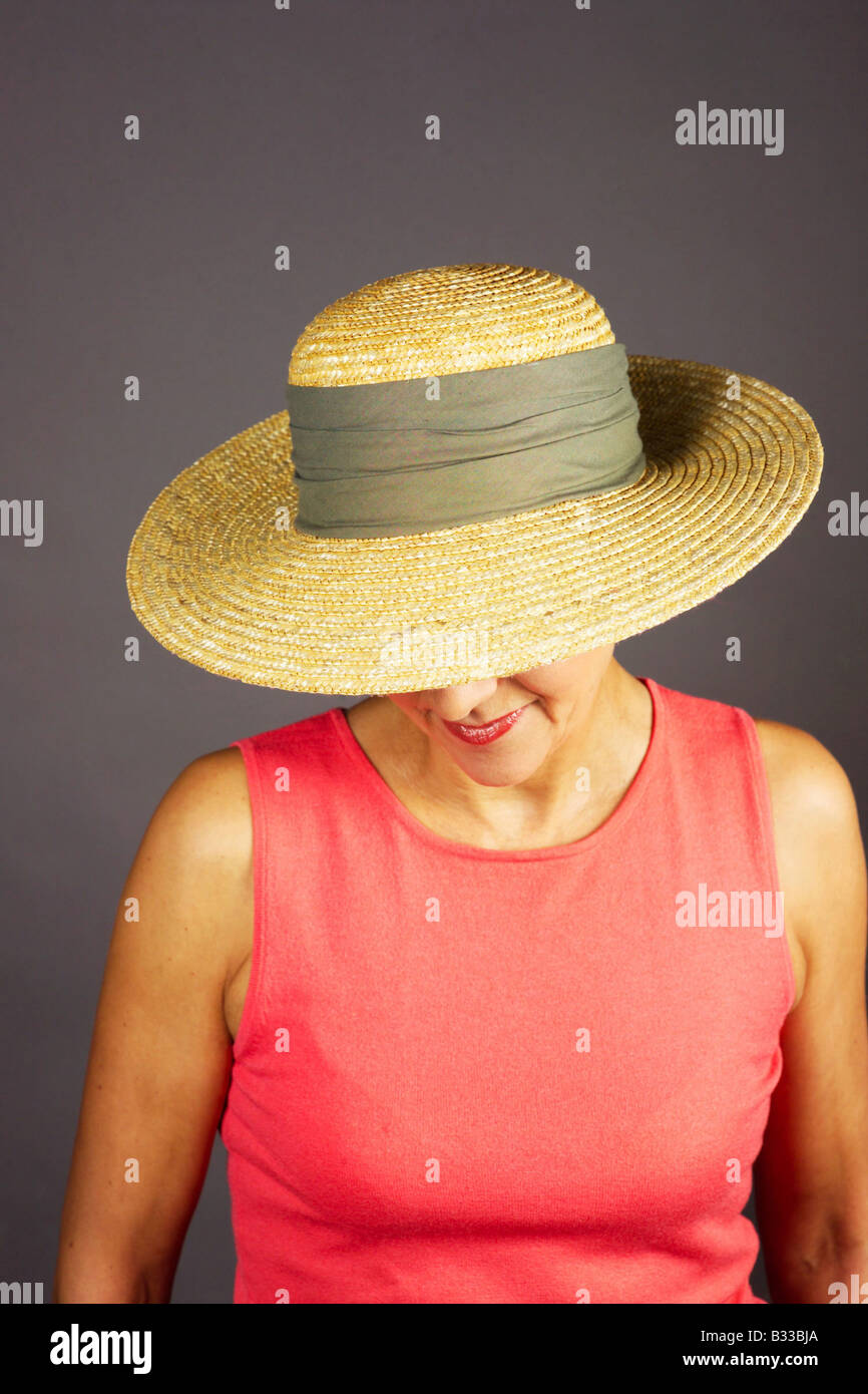 a woman summerly dressed wearing a strawhat Stock Photo