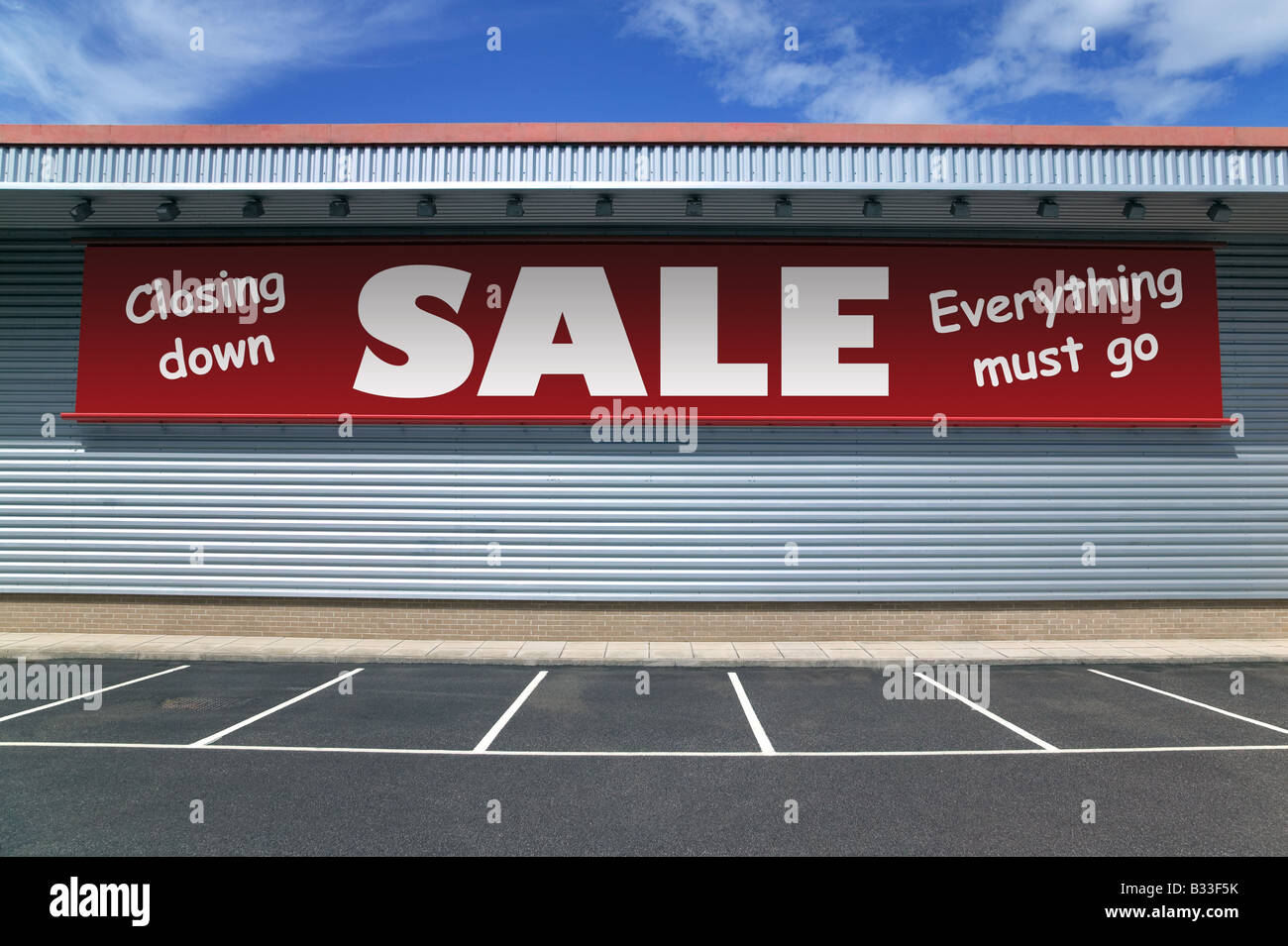 Retail building with a banner on the outside for a closing down sale Good image for recession concepts - Stock Image