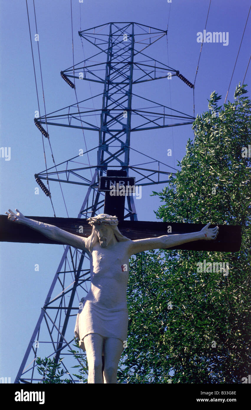 Outdoor sculptural depiction of Jesus Christ on the cross with electric power tower close in background against - Stock Image