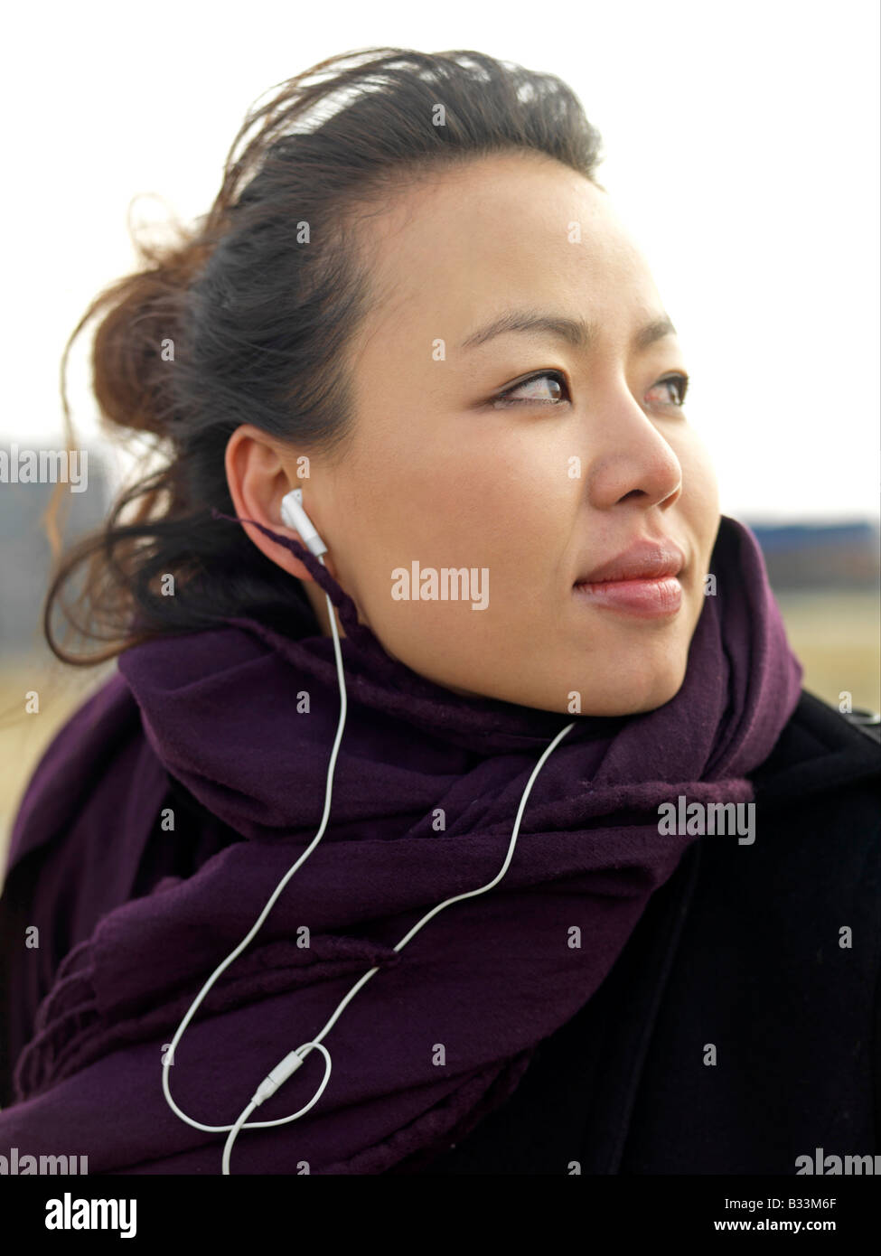 A young woman with wind swept looks away while listening to music. - Stock Image
