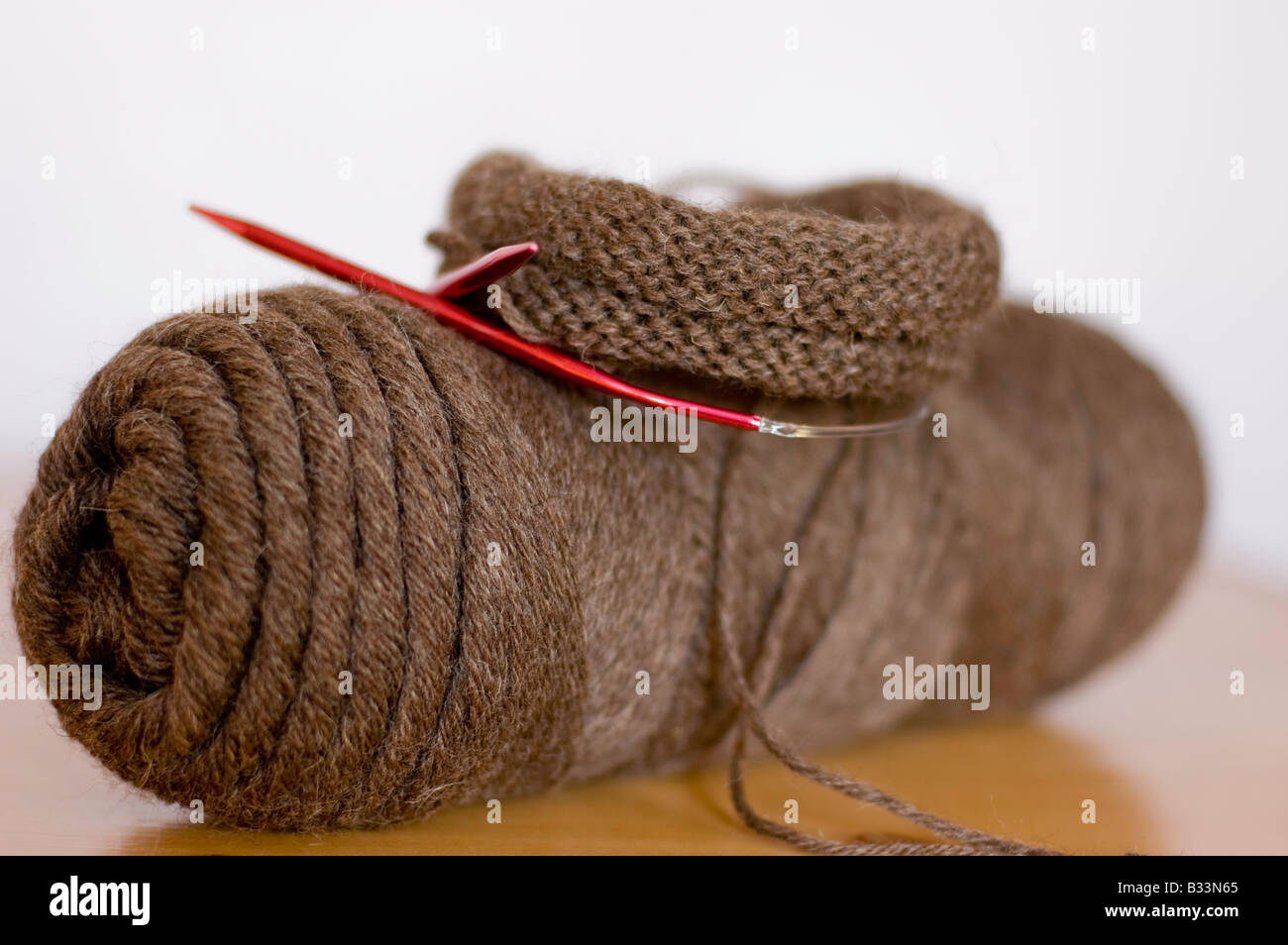Red knitting needles against a skein of brown yarn. - Stock Image