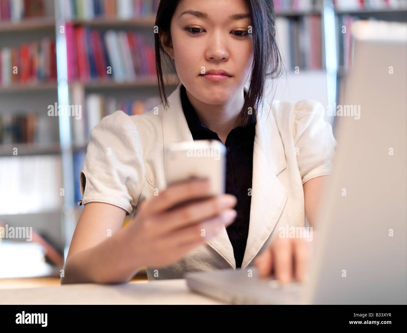 A young Asian sits at her desk working on her laptop. - Stock Image