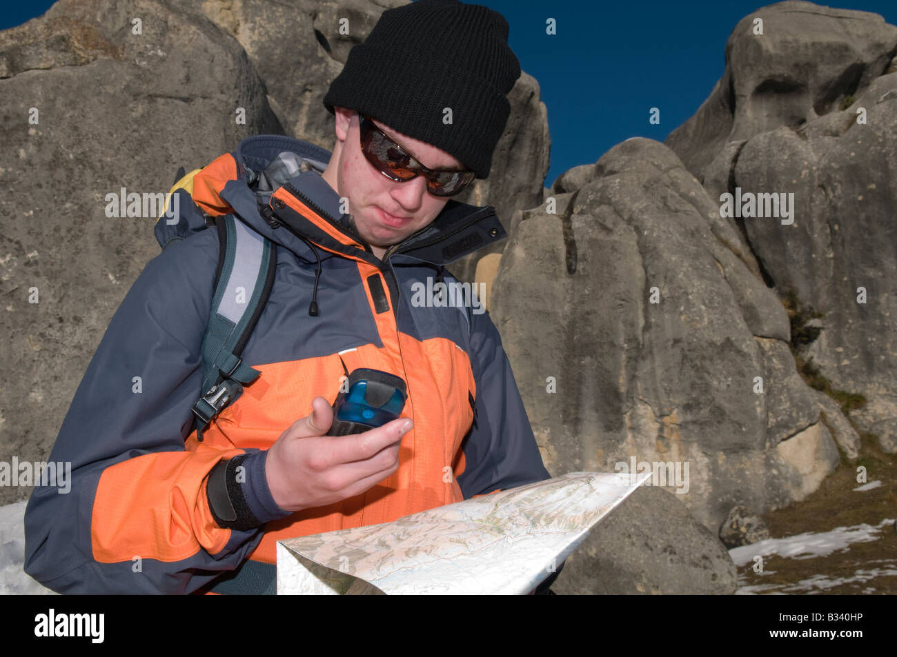 Winter hiker checks map against GPS - Stock Image